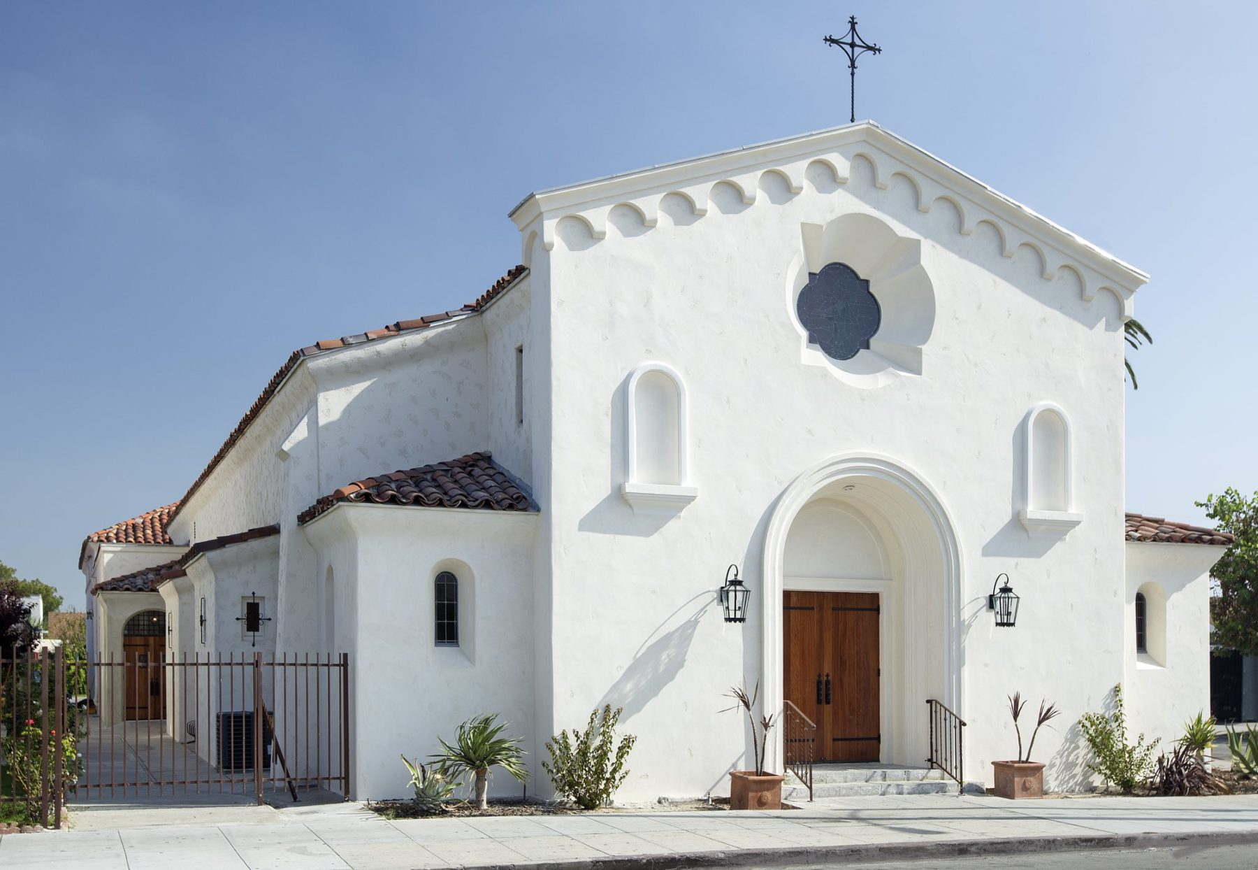 White adobe terra cotta tile mission architecture niches church façade with wood door wrought iron lights by Harrison Design