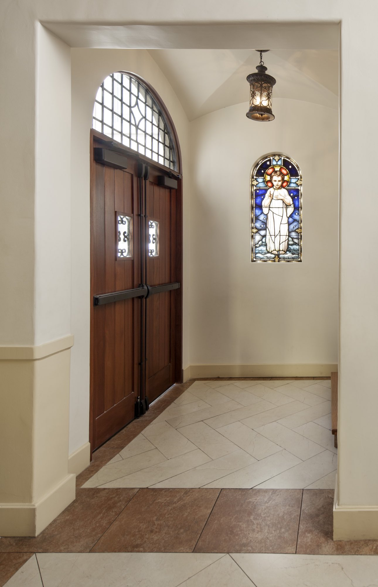 Tile floor and wooden door with wrought iron details and traditional stain glass in light filled vestibule by Harrison Design