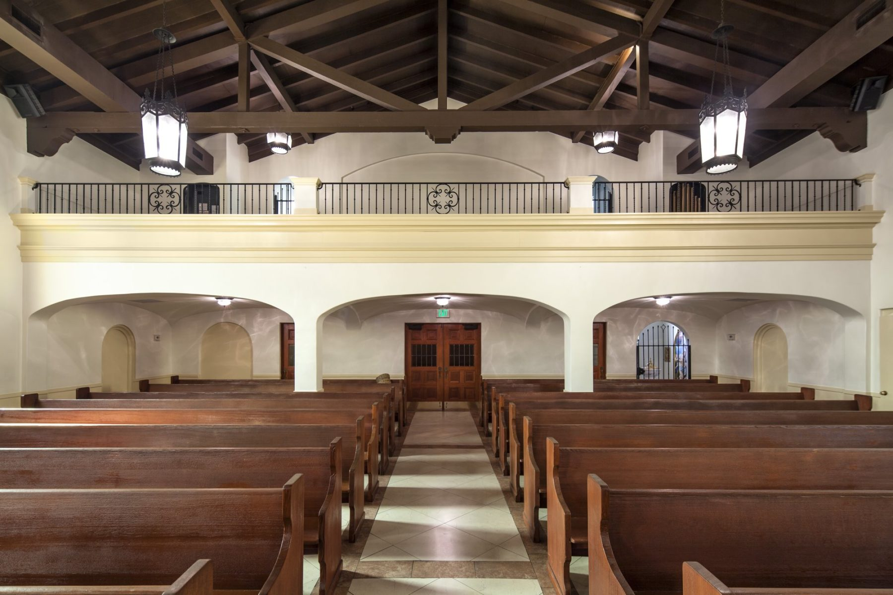 Choir loft with classical details and iron rail with heavy wooden timber trusses on brackets vestibule by Harrison Design