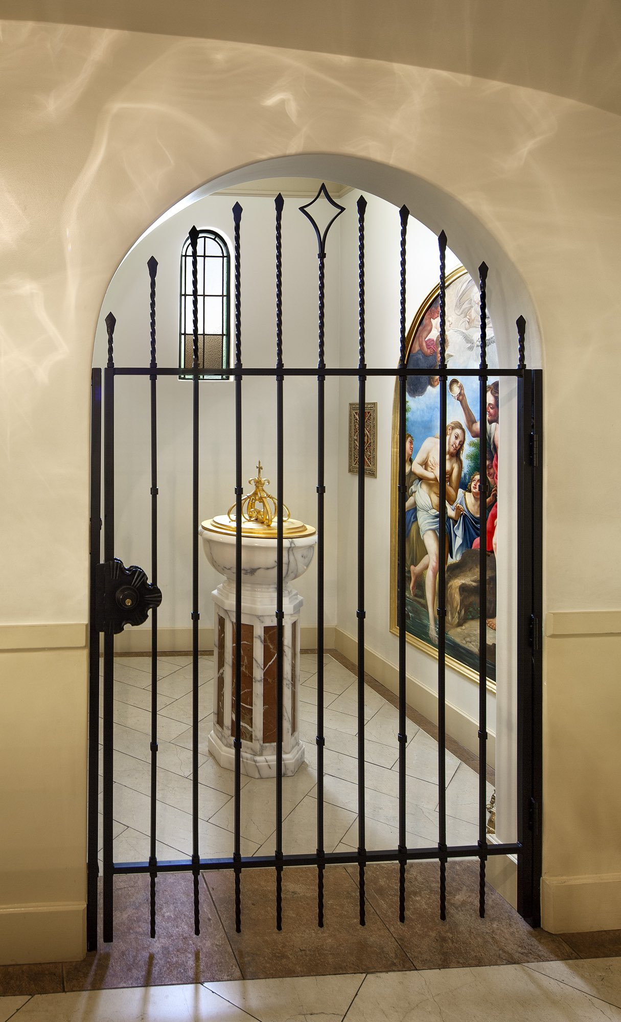 Marble baptistry holy water font wrought iron gate and baptism of the lord painting with herringbone tile by Harrison Design