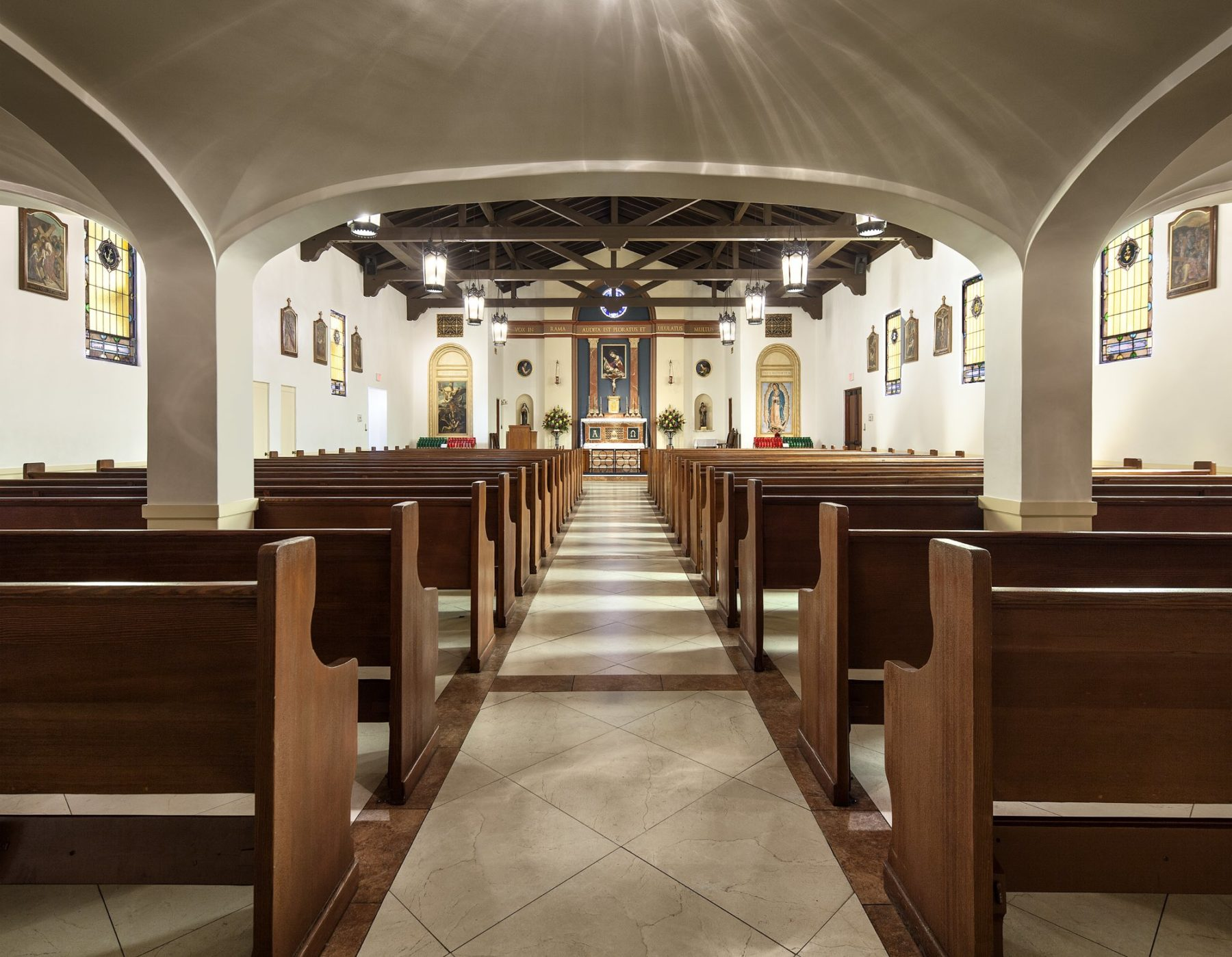 Classical nave with iron pendant hanging lanterns stations of the cross columns wooden pews stained glass by Harrison Design