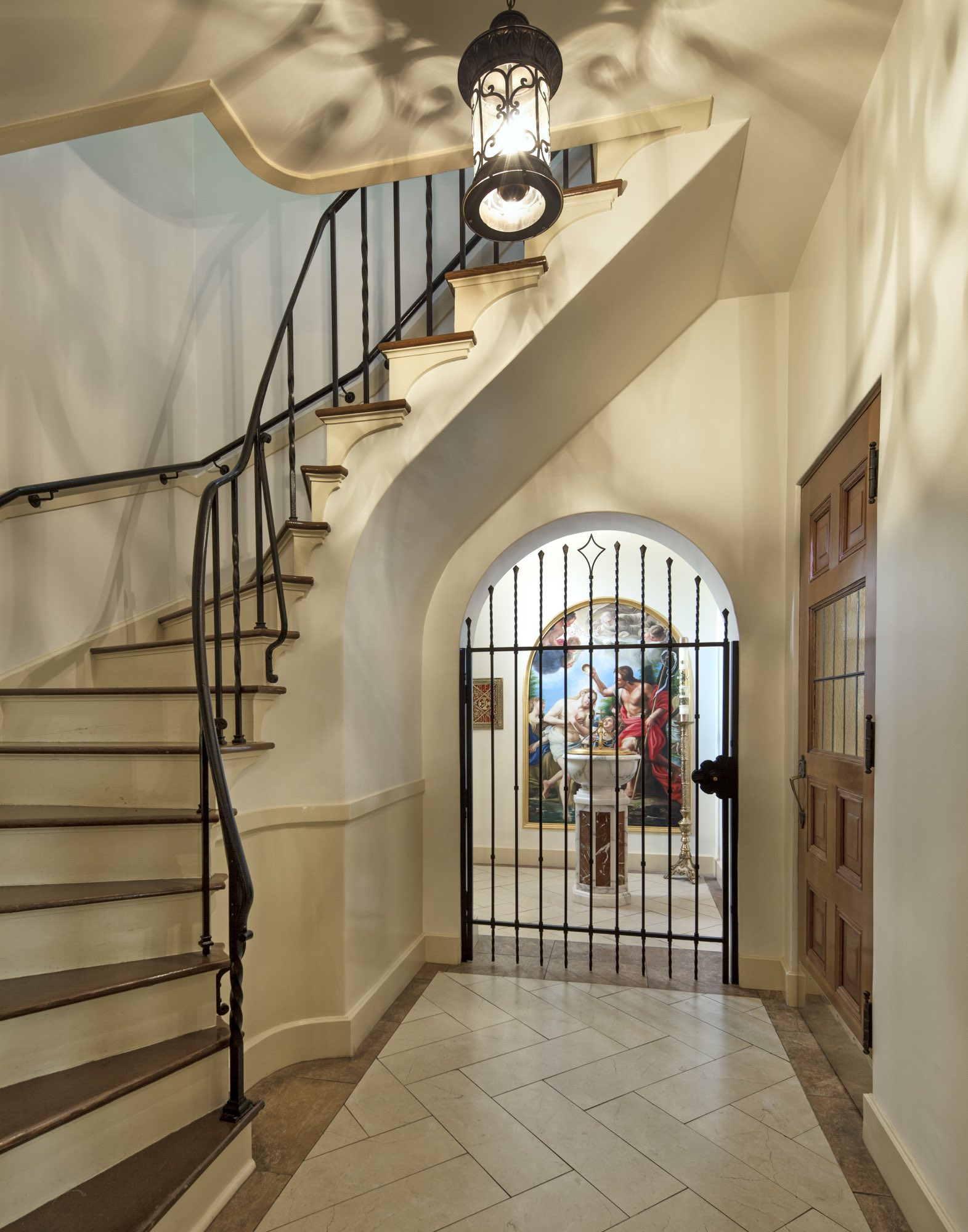 Narthex baptistry wrought iron light and choir loft stairwell stone tile floor baptism of Christ painting by Harrison Design