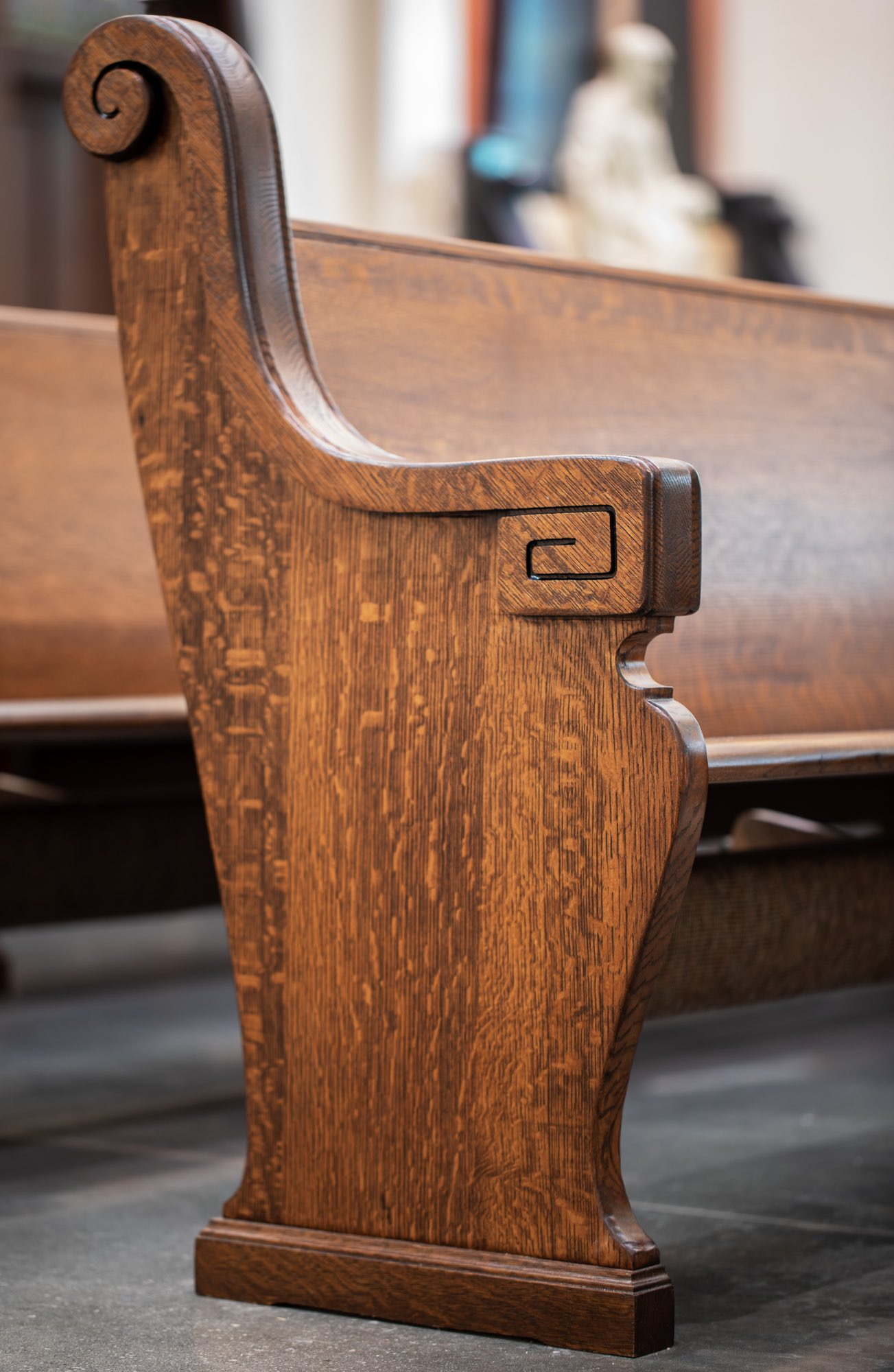 Sculptural wooden pews with carved scrolls mahogany arms and kneelers architect of record Harrison Design