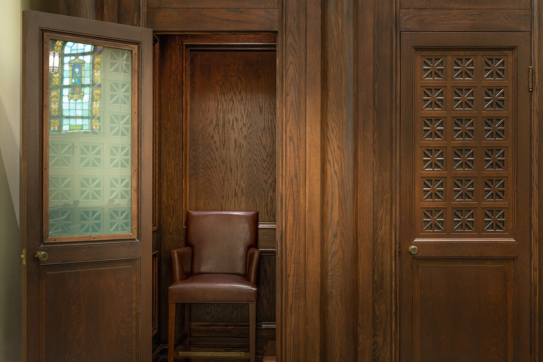 Confessional doors ornate wood pattern with soundproof glass and natural light architecture by Harrison Design