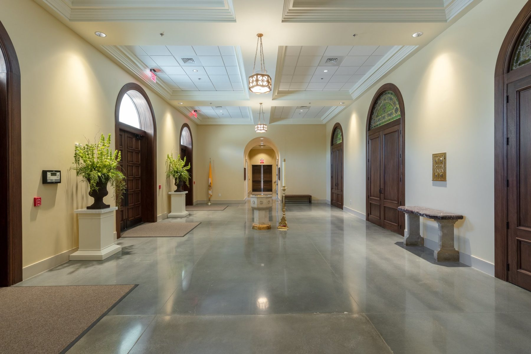 Light filled narthex with large wooden doors holy water font and easter candle classical details by Harrison Design