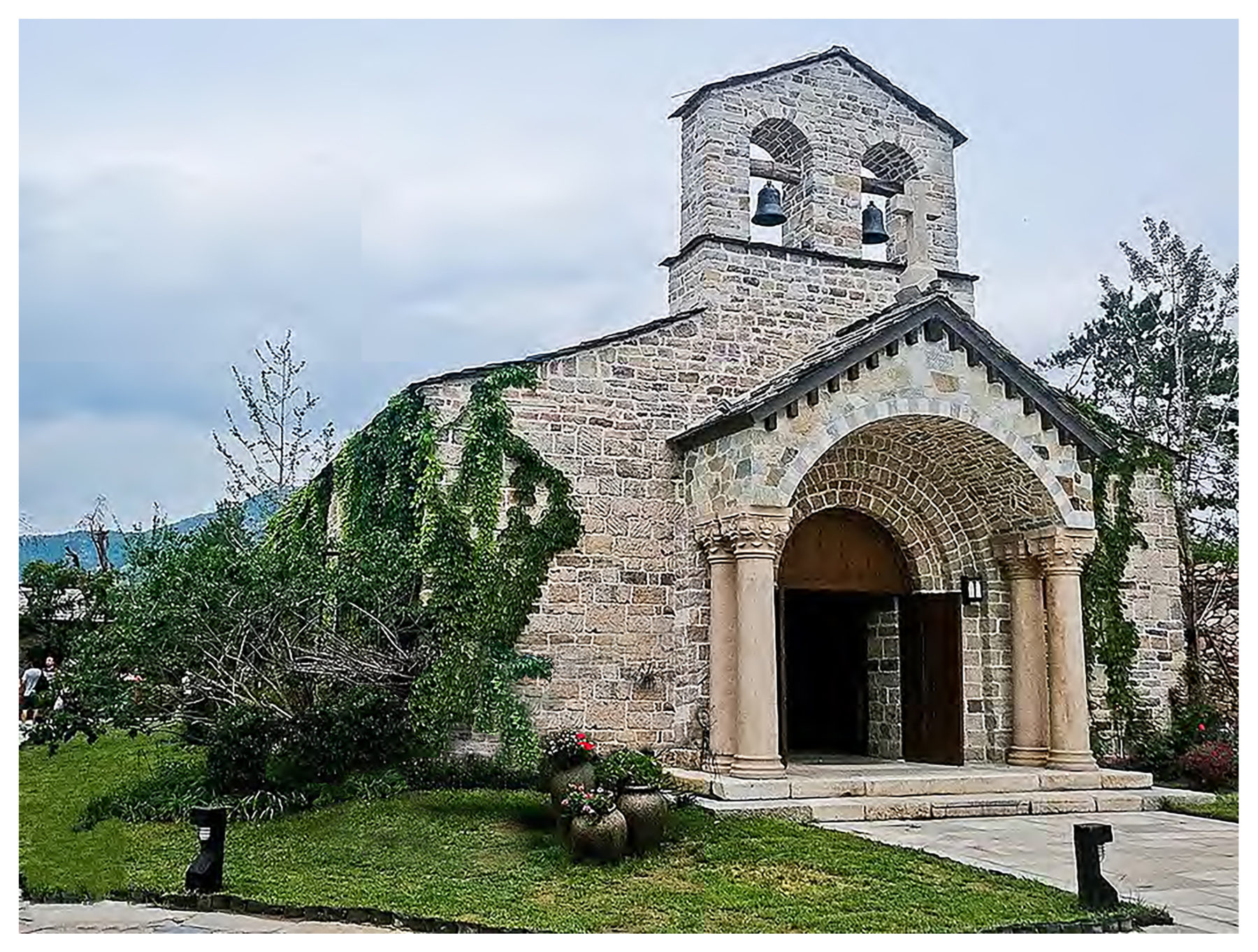 Traditional mission church stone architecture with Corinthian columns porch and stone arches double belfry by Harrison Design
