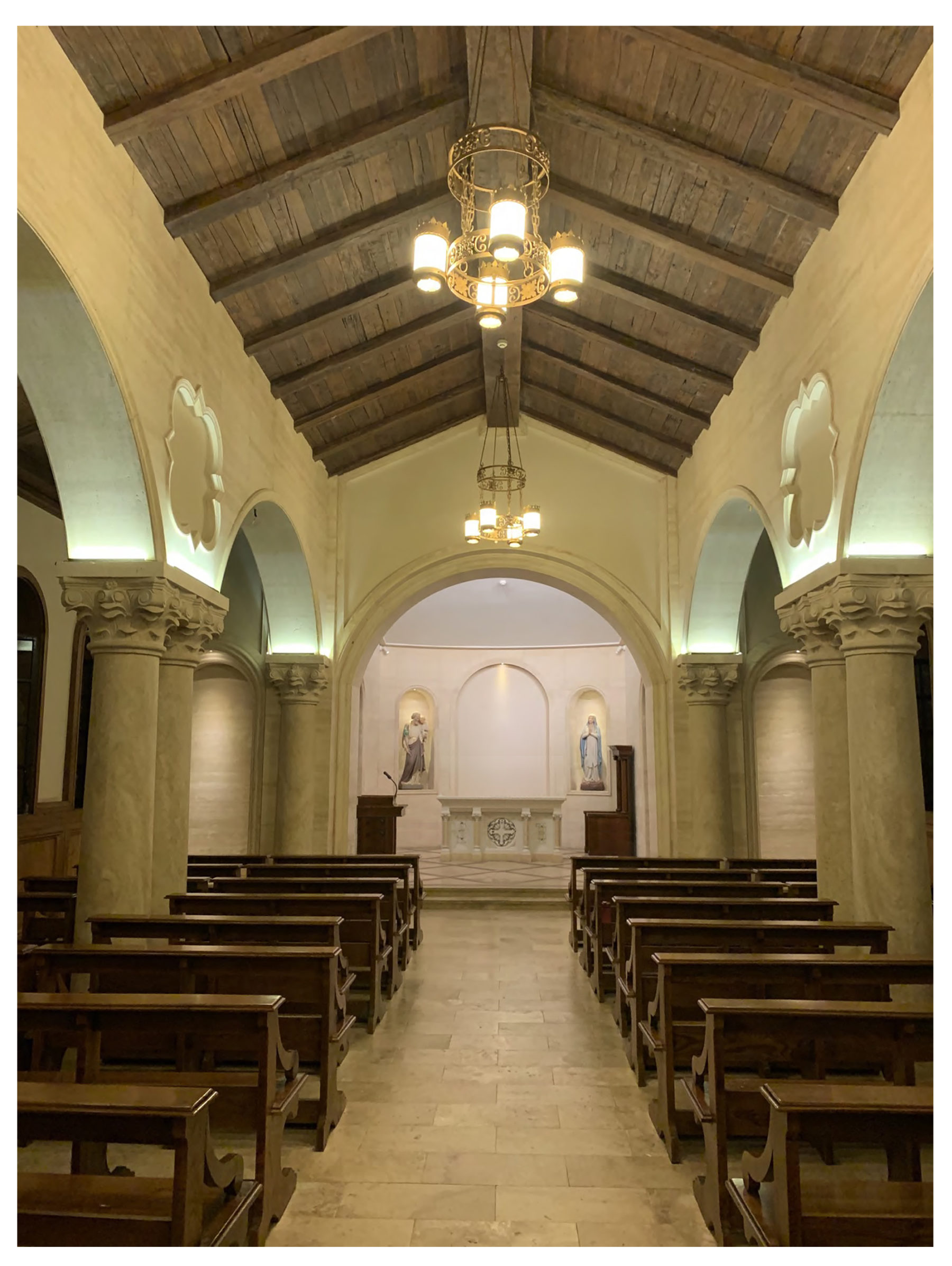 Wooden timber nave ceiling with arches on columns and ornate classical details wooden pews and stone by Harrison Design