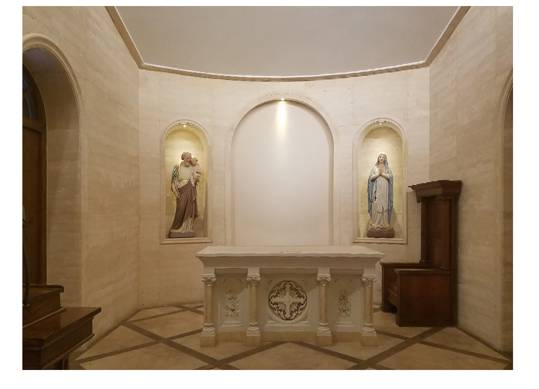 Stone sanctuary with altar columns saint statue niches and travertine finish diamond ribbon floor by Harrison Design