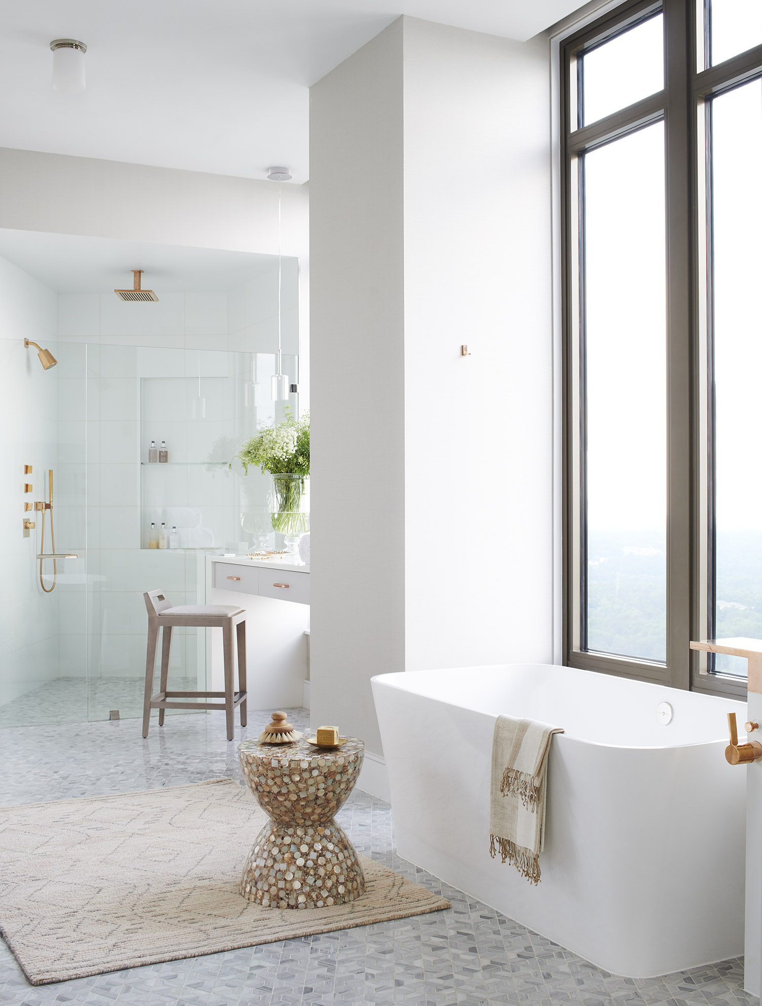Spa like bathroom with a view features an intricate marble mosaic tile floor and unexpected rose gold fixtures.