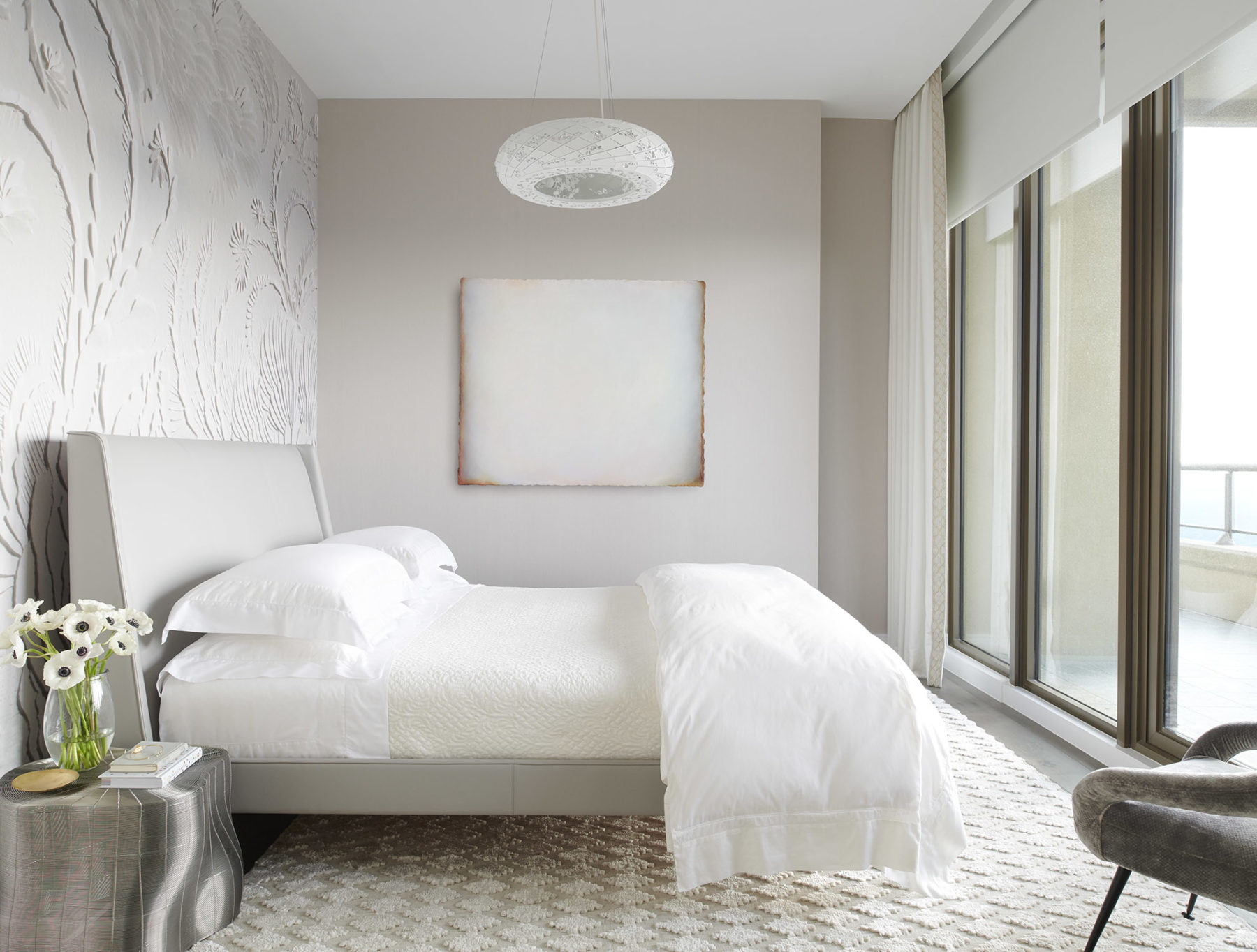 Ethereal bedroom in an apartment designed by Harrison Design with Poltrona Frau bedframe and Phillip Jeffries wall treatment.