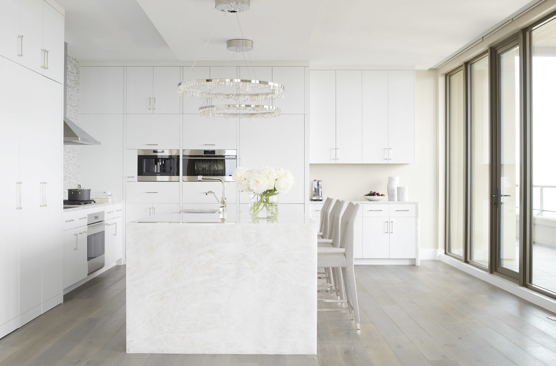 All white modern kitchen with quartzite island, Subzero Wolf appliances and stainless accents. Interior by Harrison Design.