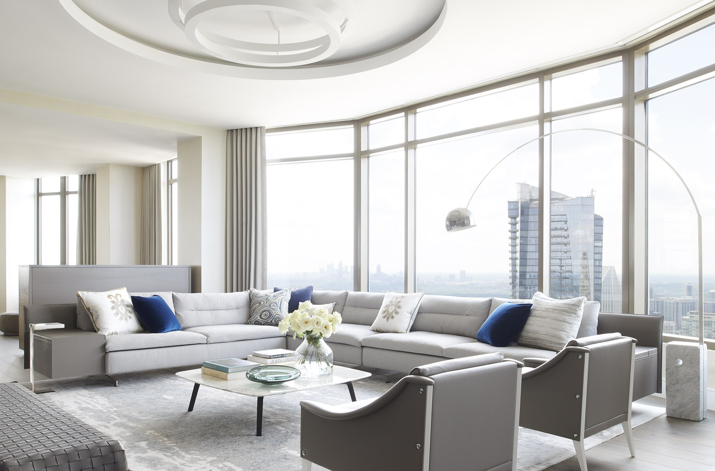 Modern living room with floor to ceiling windows featuring contemporary Italian furniture. Interiors by Harrison Design.