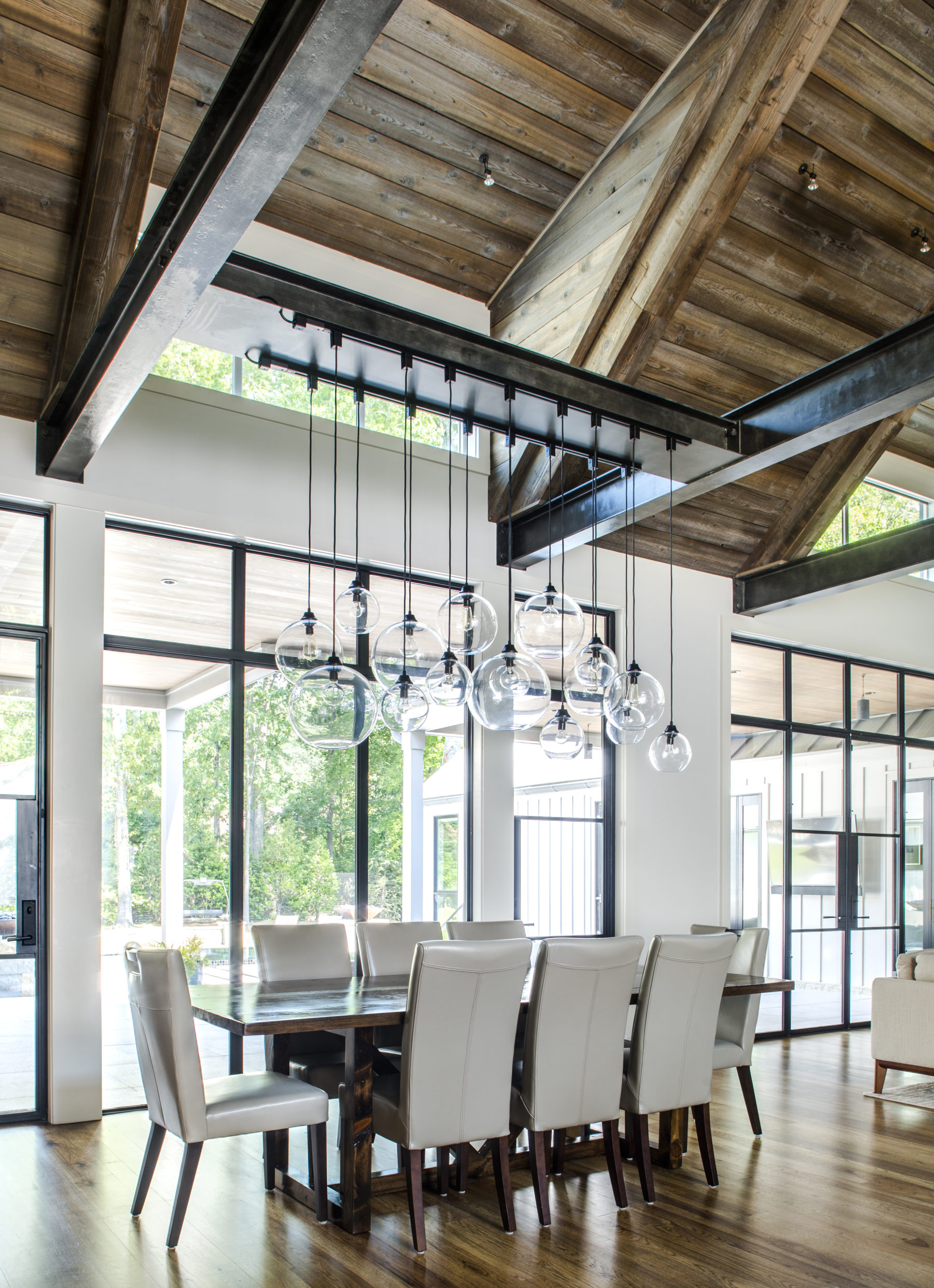 Metal framed windows, glass doors and transoms create a striking open dining area with hickory floor by Harrison Design.