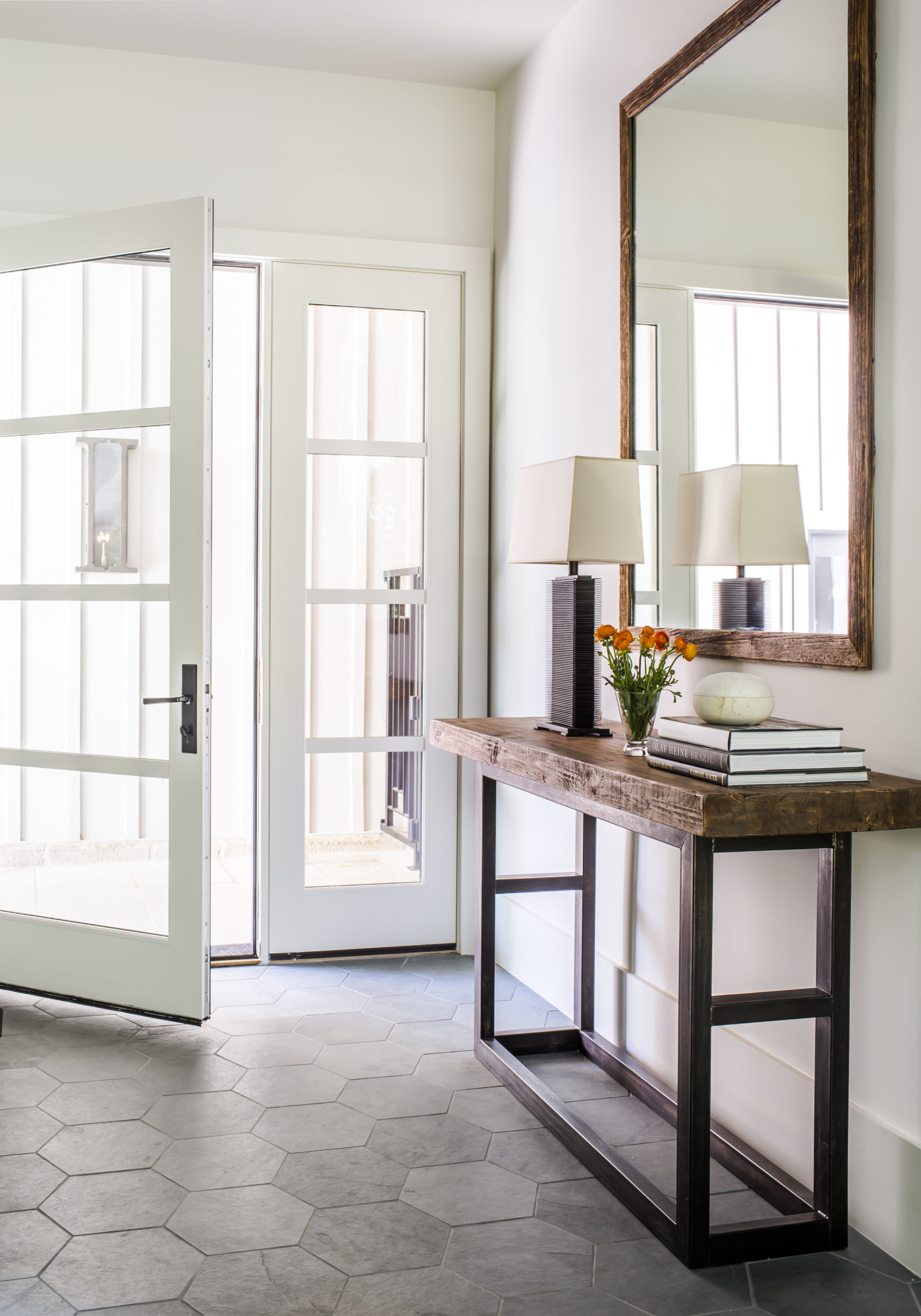 Harrison Design used a glass paned front door and sidelight window to create a sun filled foyer reflected by the mirror