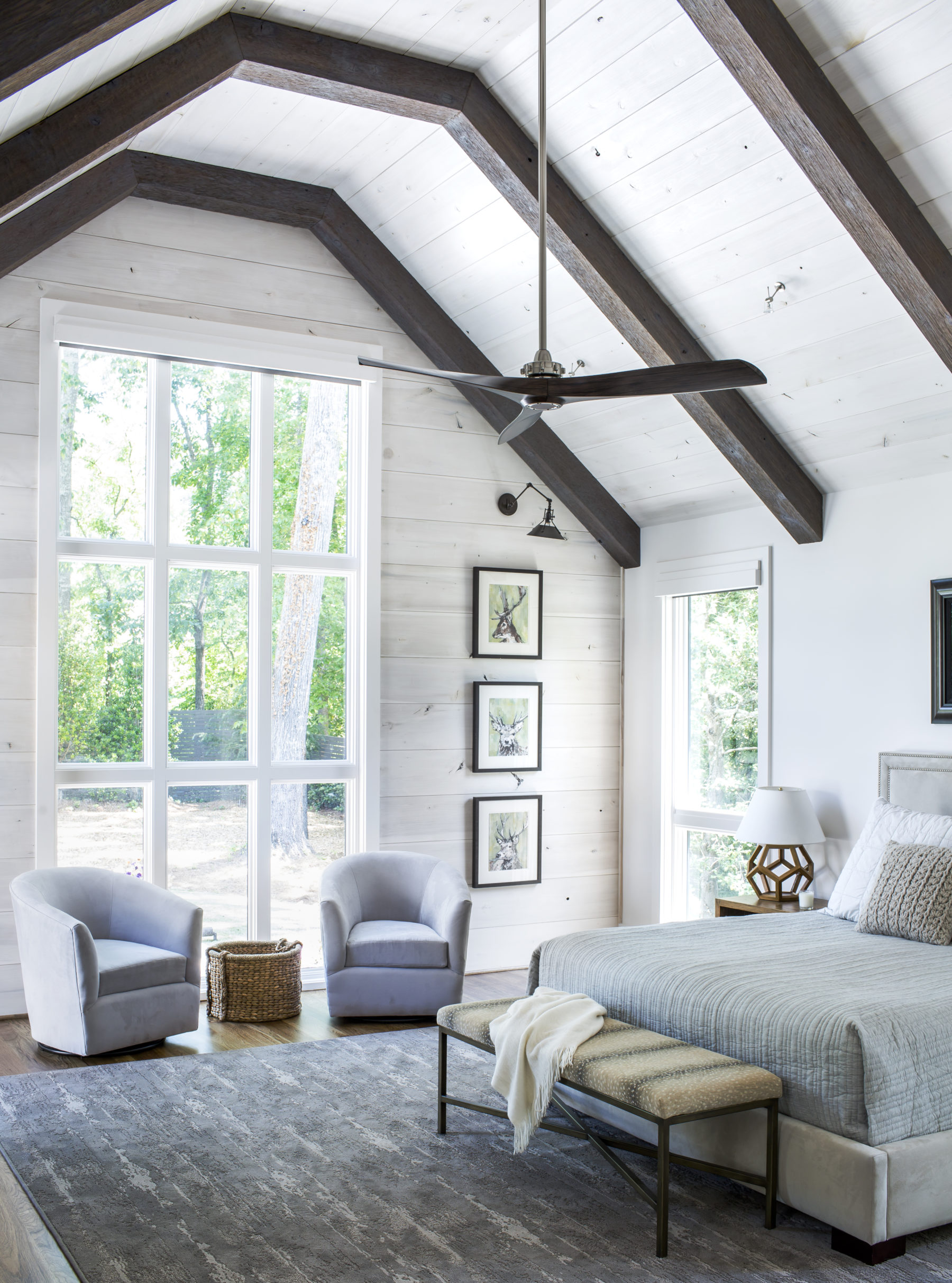 Dark beams, whitewashed shiplap wall and ceiling in bedroom by architects Harrison Design with streamlined ceiling fan