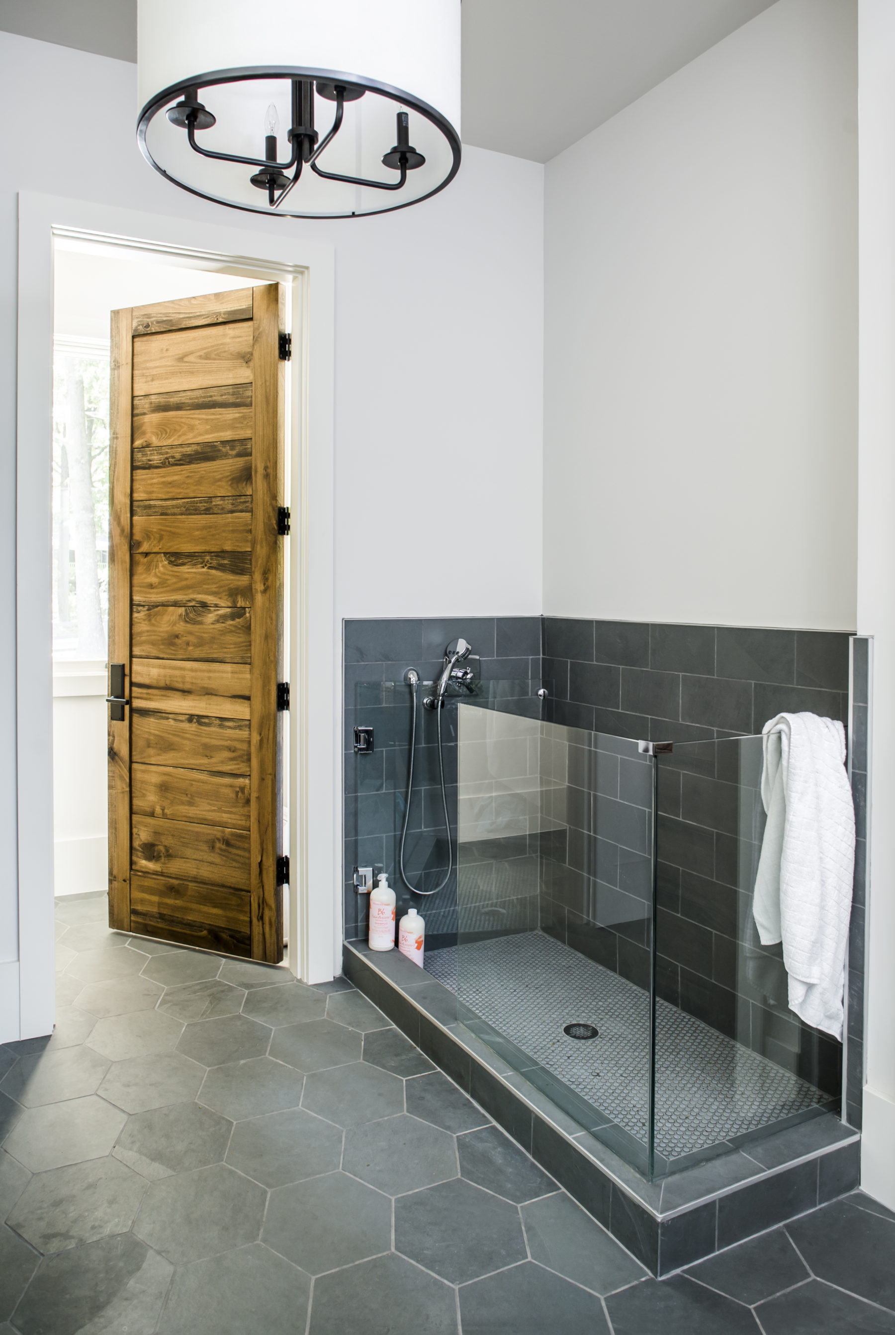 In residence by Harrison Design, the mudroom includes dog wash with slate hexagonal easy cleaning tile