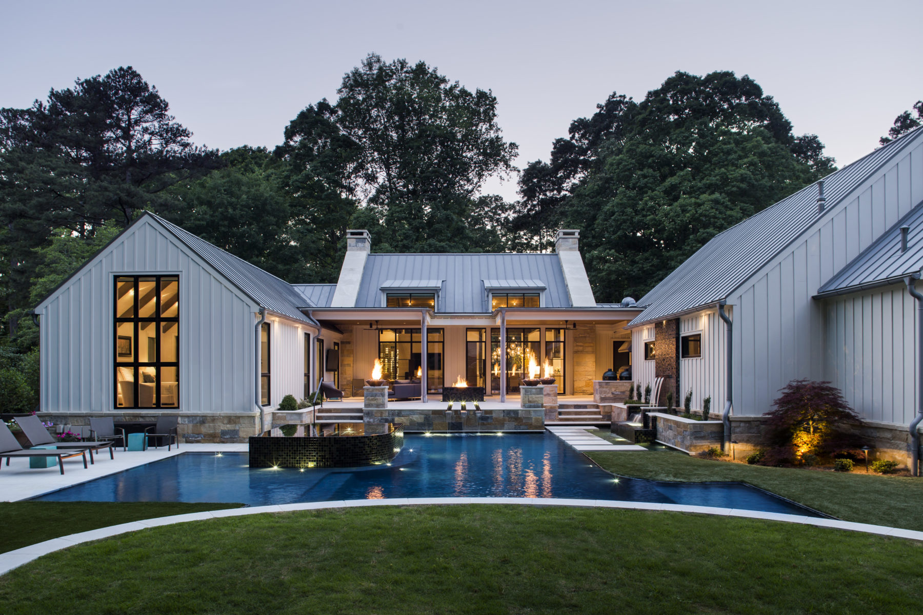 By Harrison Design Atlanta, triple height windows, a spacious covered terrace and oasis style pool create an outdoor paradise
