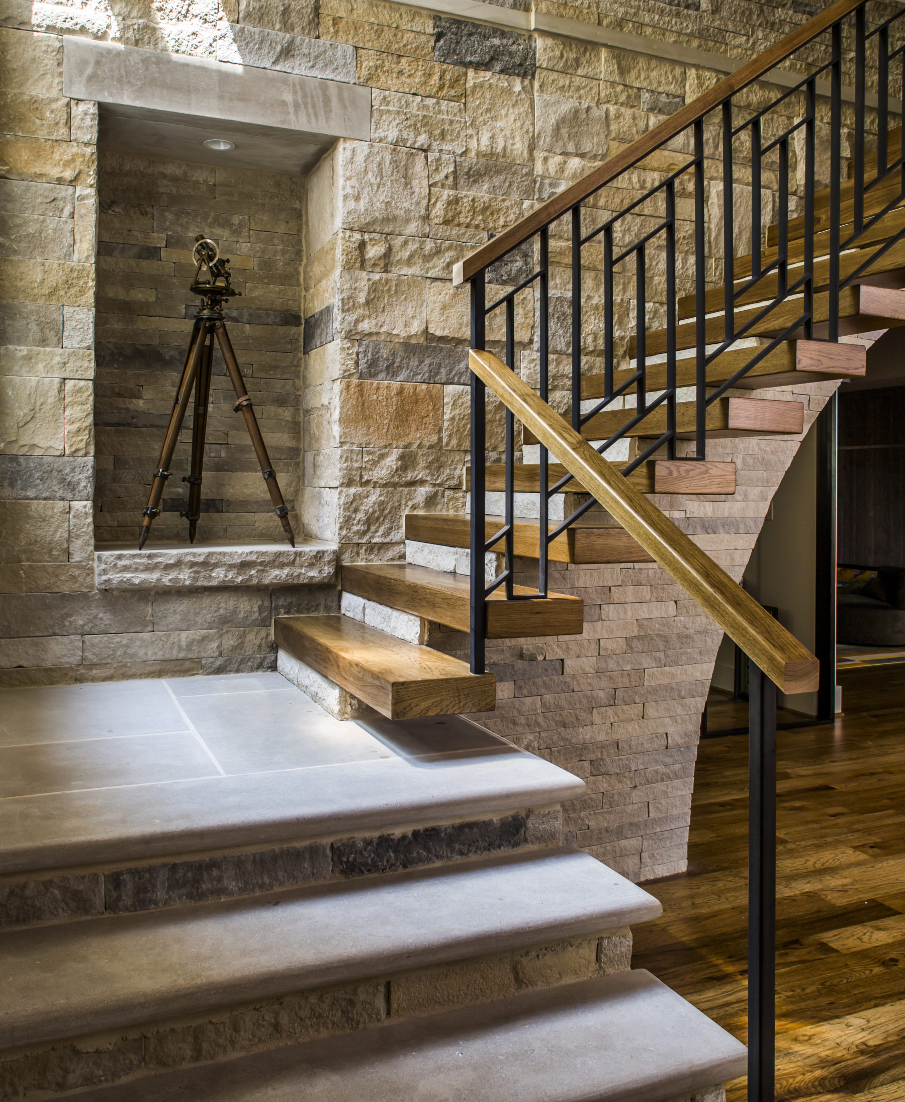 Wood stair treads cantilever from the stone leading to a fully finished spacious basement designed by Harrison Design