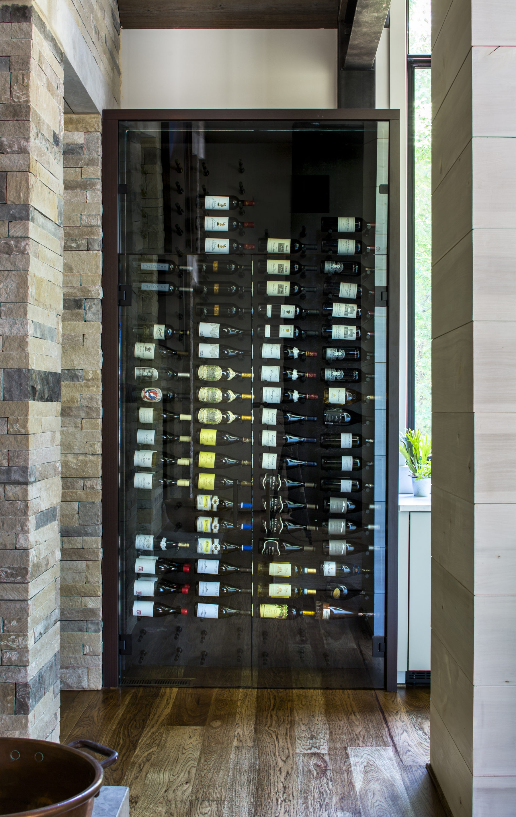 Custom refrigerated wine wall saves space and cleverly stores wine in this home interior architecture by Harrison Design
