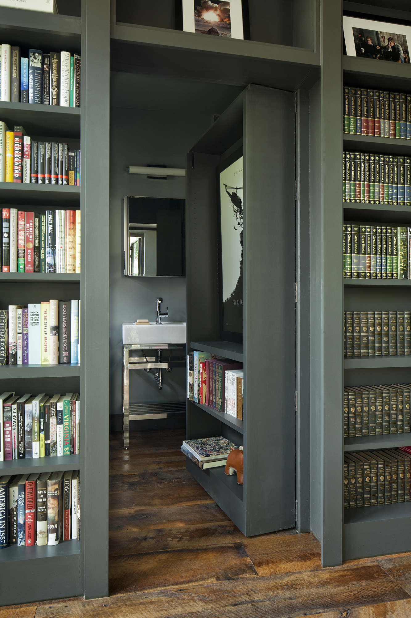 Rolled open, the gunmetal bookcase reveals a half bathroom in this writer