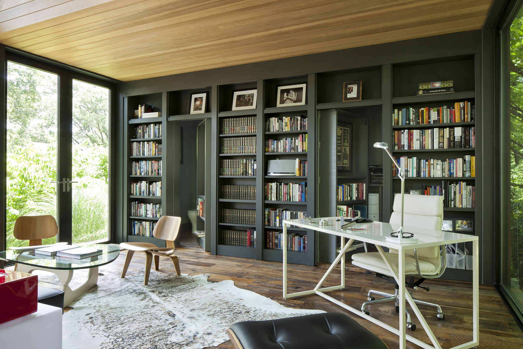 Cleverly designed gunmetal bookcases by Harrison Design roll open to expose a half bath and storage
