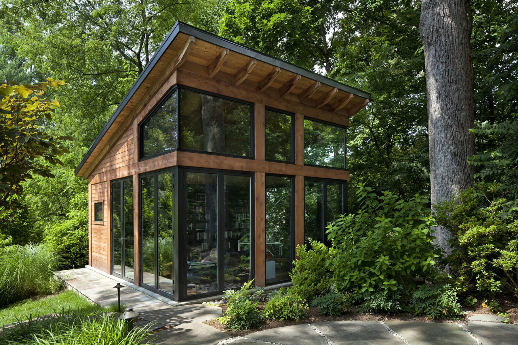 Cornered windows, glass doors and transoms expose Harrison Design glass cabin to the woods and enhance sense of place