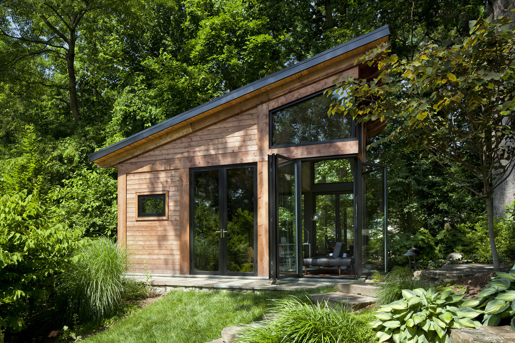 With cedar cladding, architects at Harrison Design angled roofline to heighten sense of volume of small backyard studio