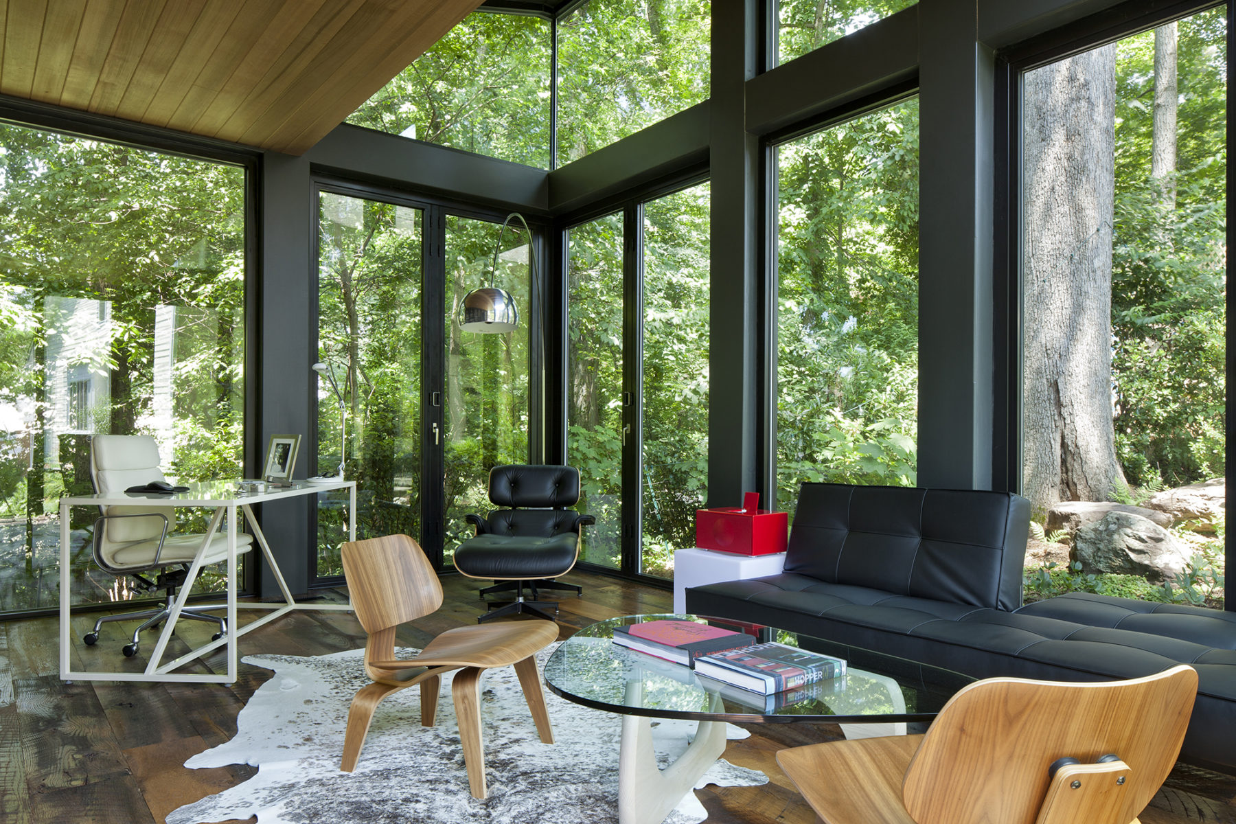 Expansive windows and a row of transoms create an ideal home office with modern architecture by Harrison Design