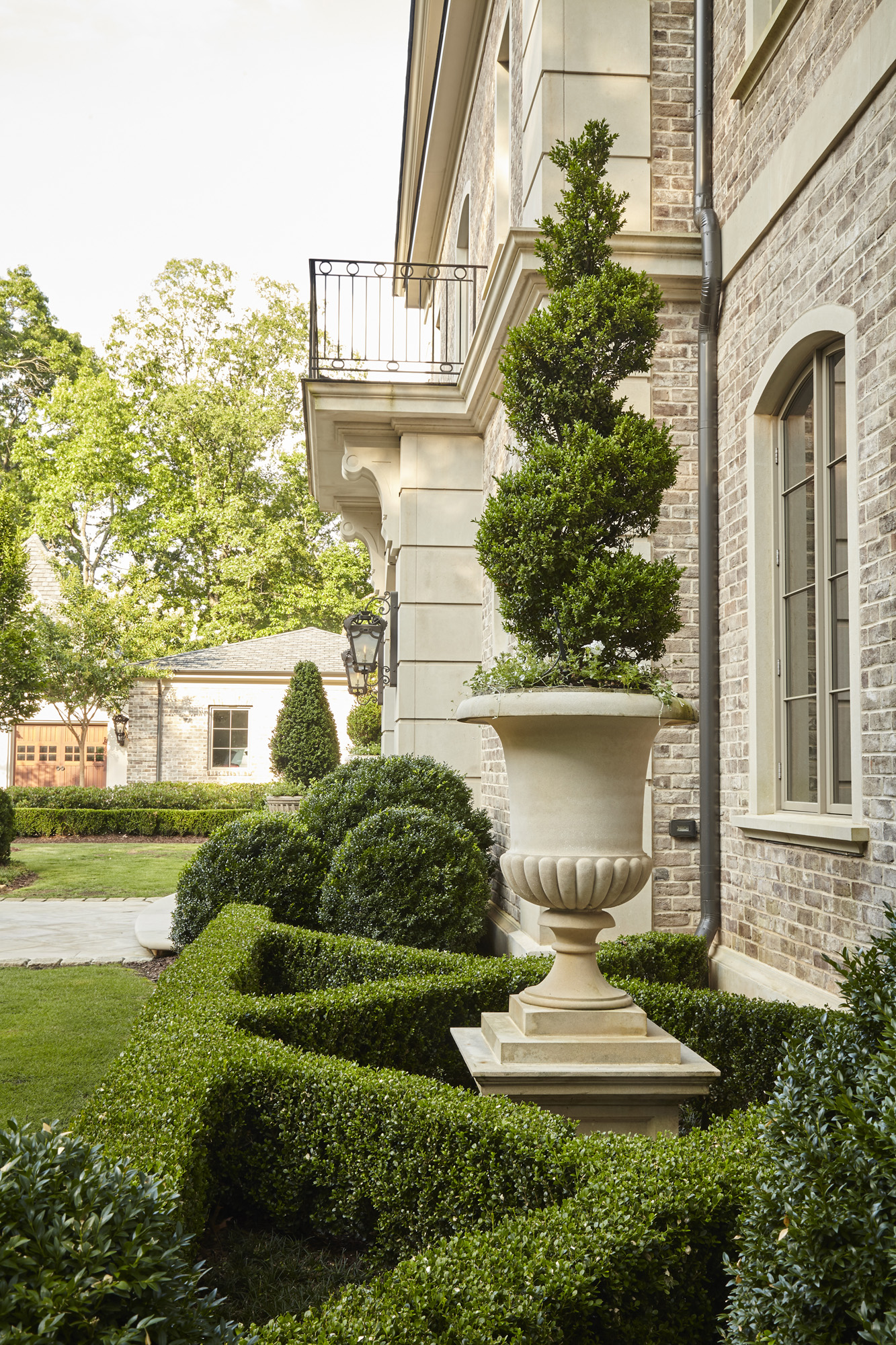 Manicured boxwood parterre urn and topiary in front of traditional French residential architecture by Harrison Design
