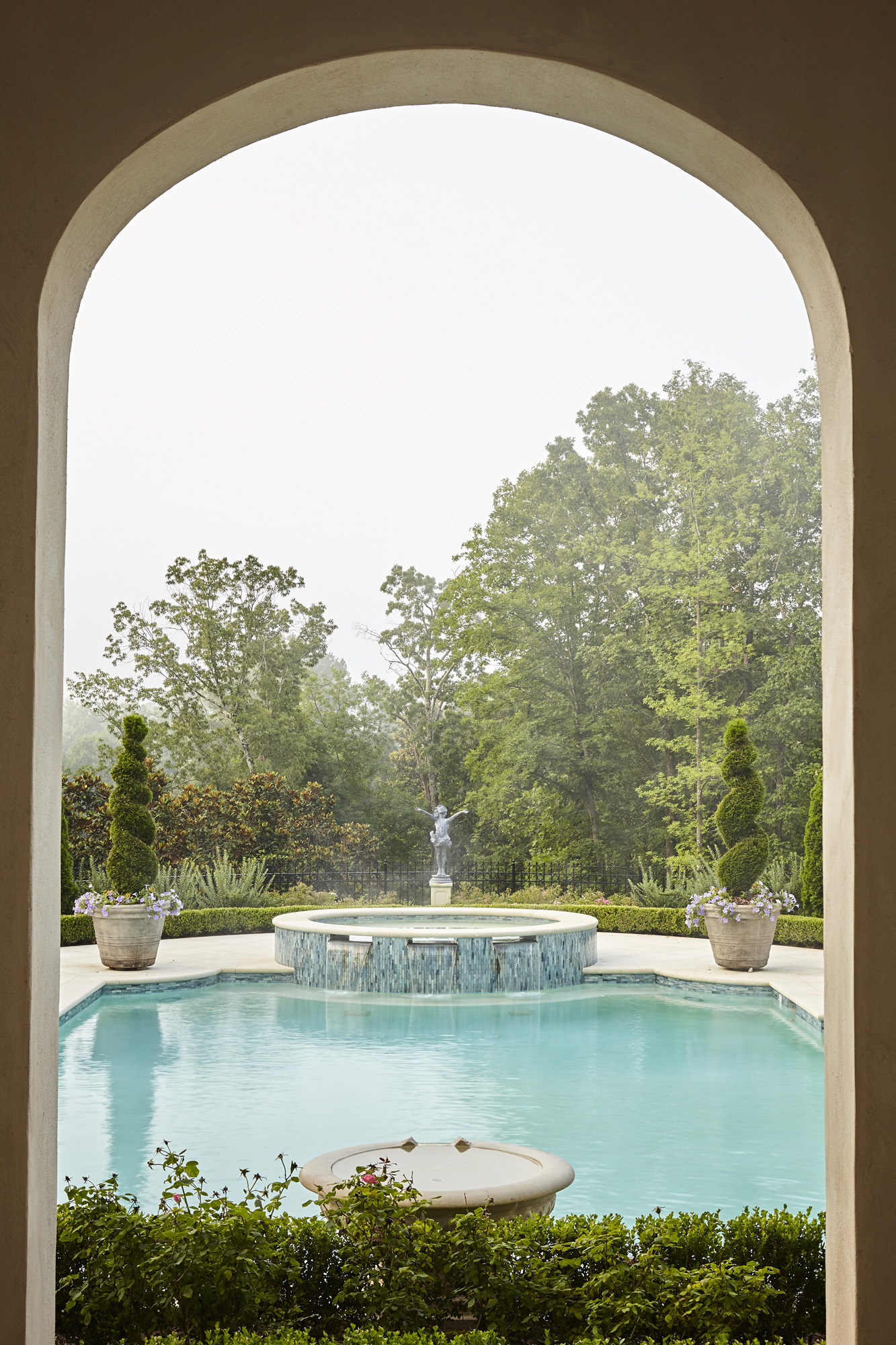 Arched opening on loggia frames pool spa statue and view on axis point a hallmark of European design by Harrison Design