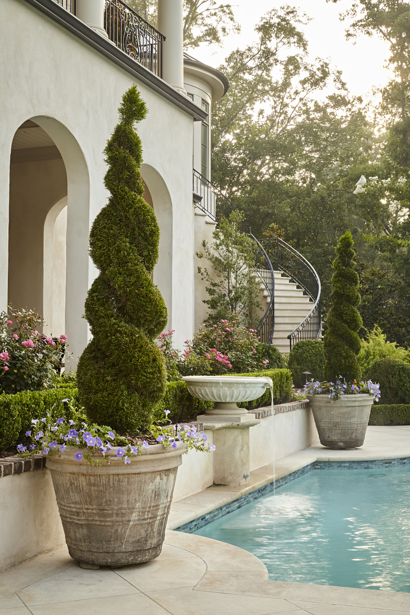 Stone urns and planters contain ornamental topiaries with shell basin fountain in Harrison Design classical French garden