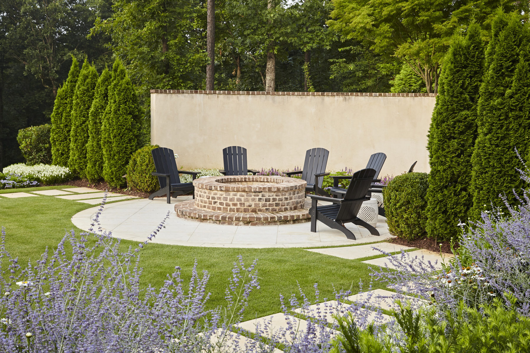Stucco and brick edged garden wall with paving stones leading to cozy brick firepit at Harrison Design traditional home