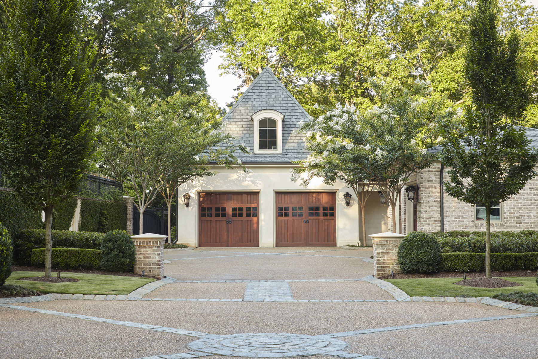 Primary entrance court to detached garage by Harrison Design with granite cobblestones horn beams and white crape myrtles