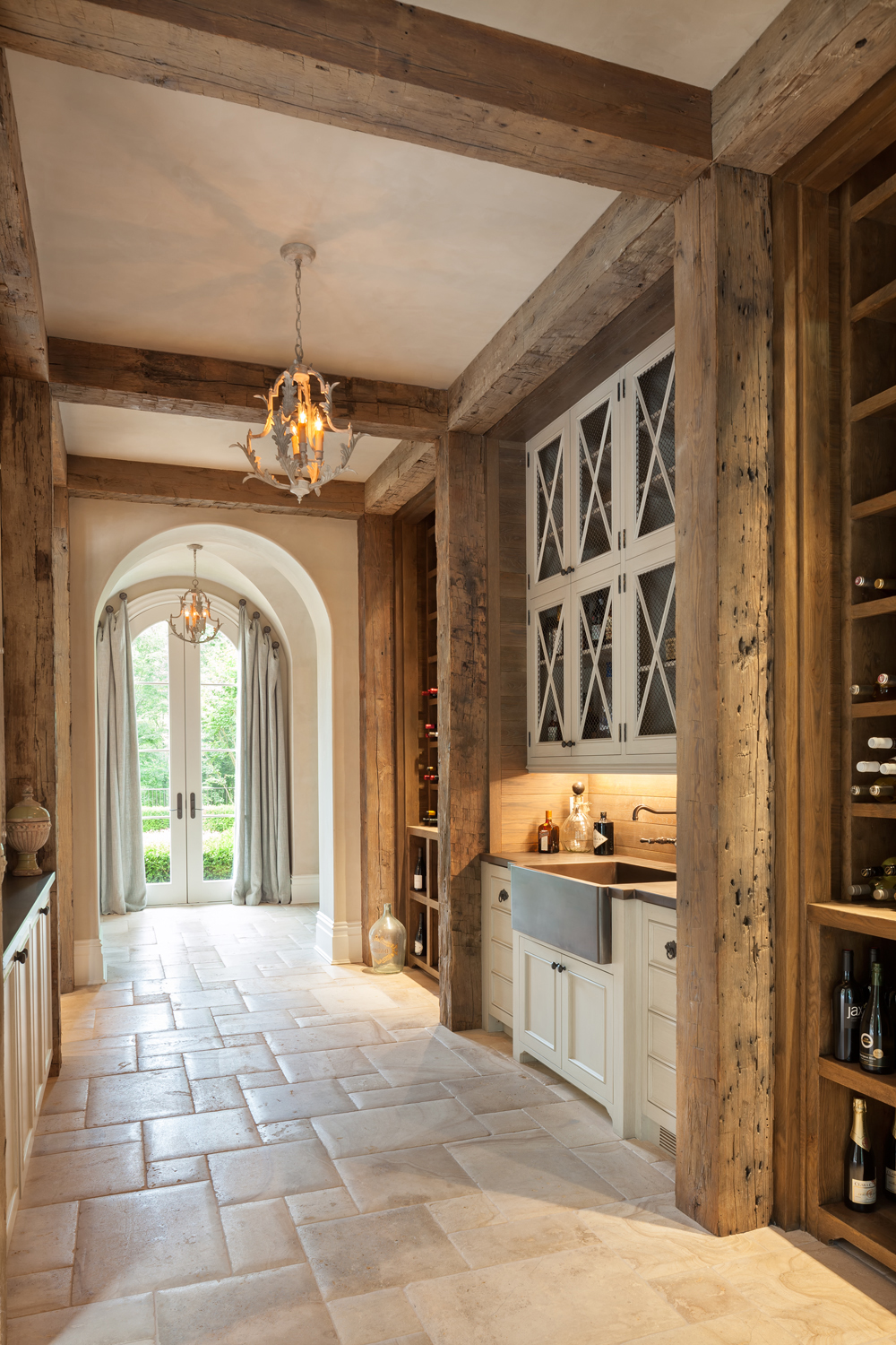 Wide hall serves as bar and wine gallery with open wine storage of Harrison Design classical farm style abode