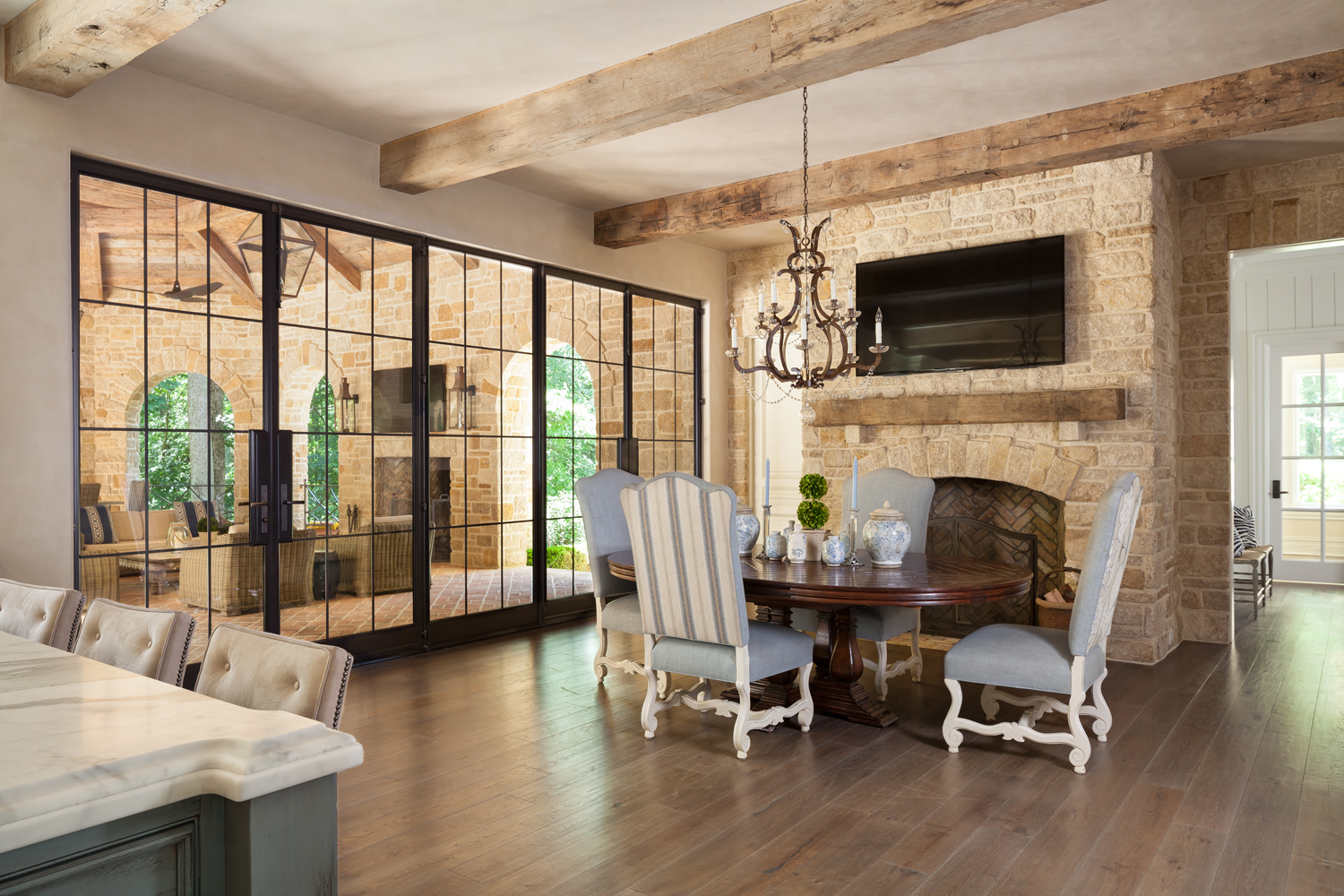 Wall of steel and glass doors connect loggia to breakfast room with reclaimed timber mantle on fireplace by Harrison Design