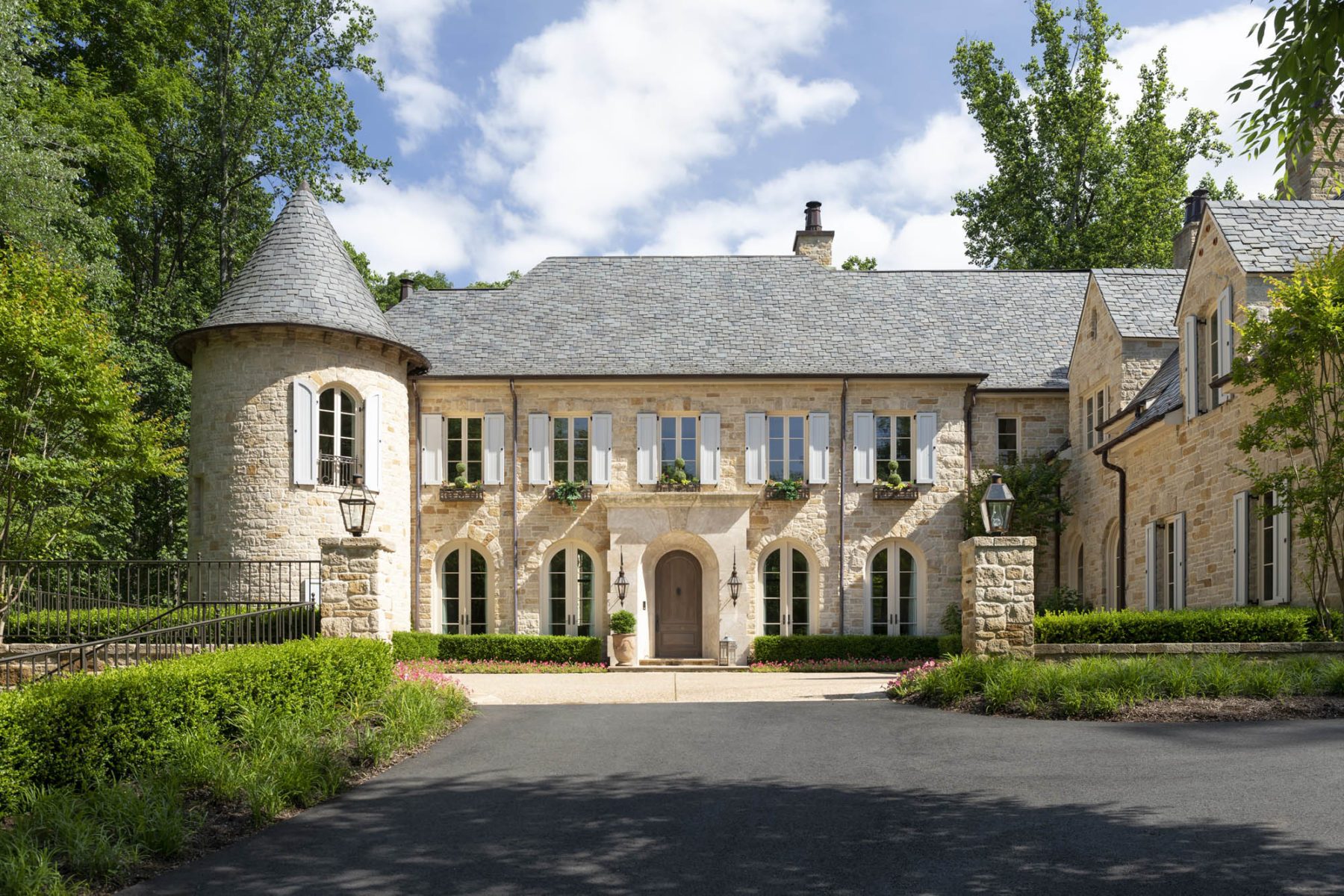 Harrison Design rough fieldstone exterior with pedimented cut limestone surround on front door and Provençal blue shutters