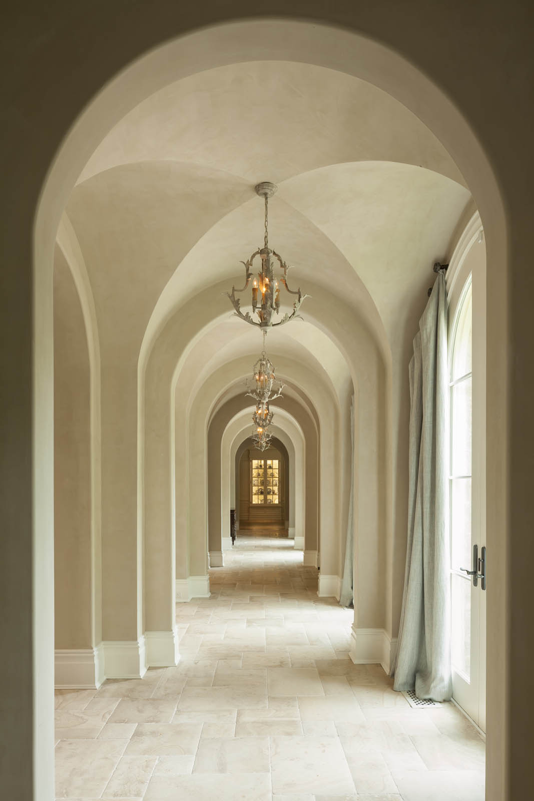 Interior architecture by Harrison Design includes cross groin vault entry hall with stone floor and arched glass doors