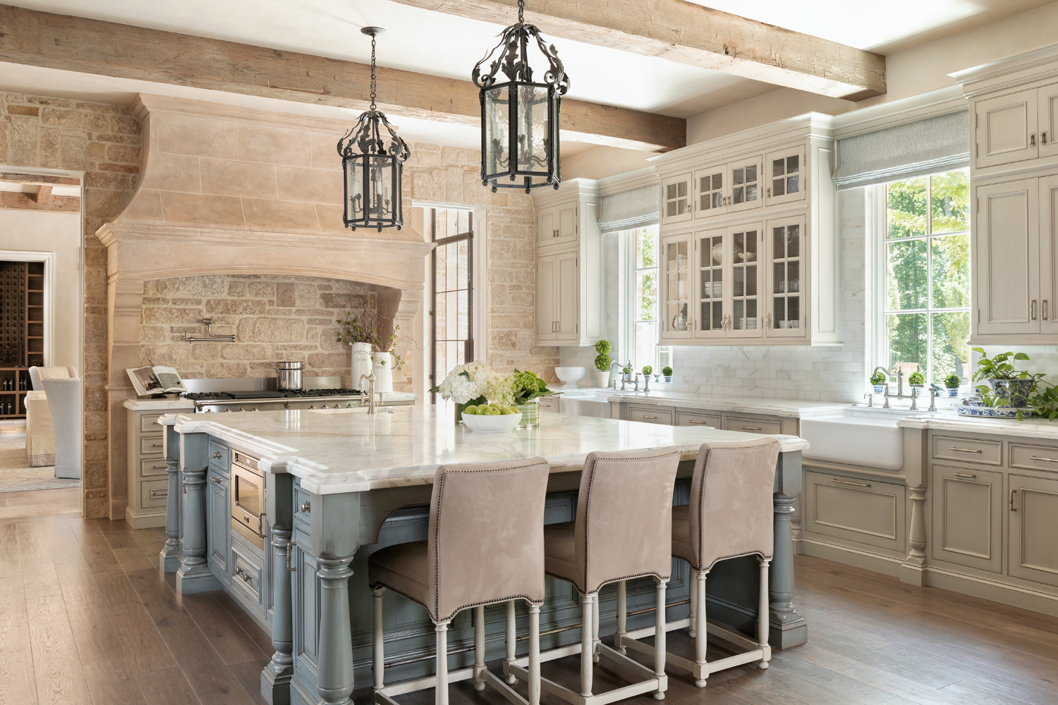 Hood mimics Norman fireplace and wood plank floors in Harrison Design kitchen with big center island glass paned cabinets