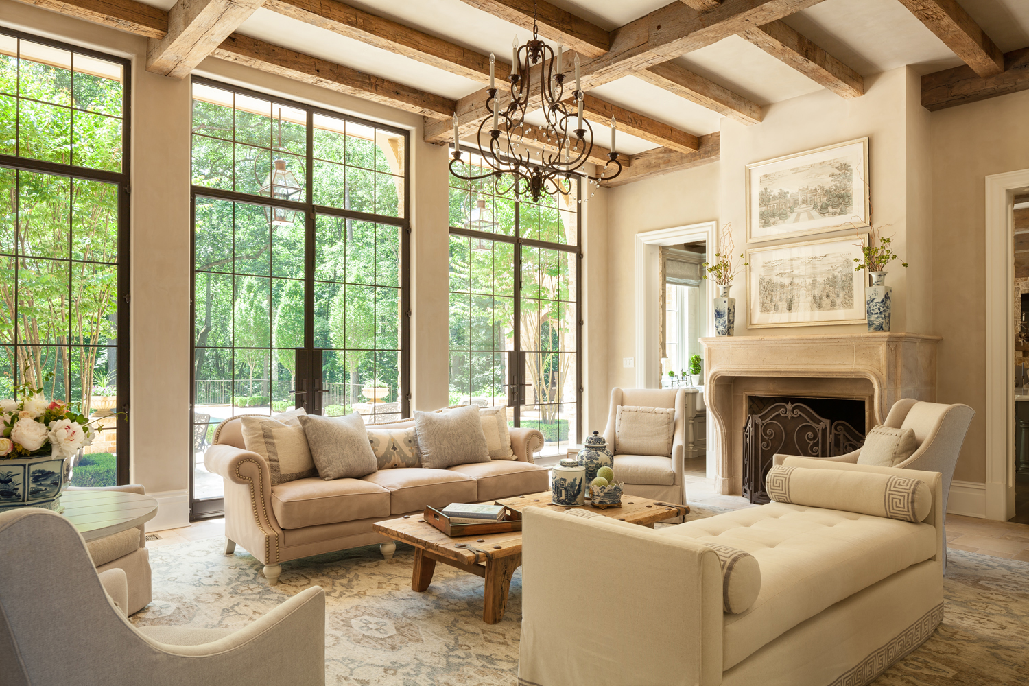 Harrison Design interior living room architecture with reclaimed heavy timber beams and steel framed glass doors to terrace