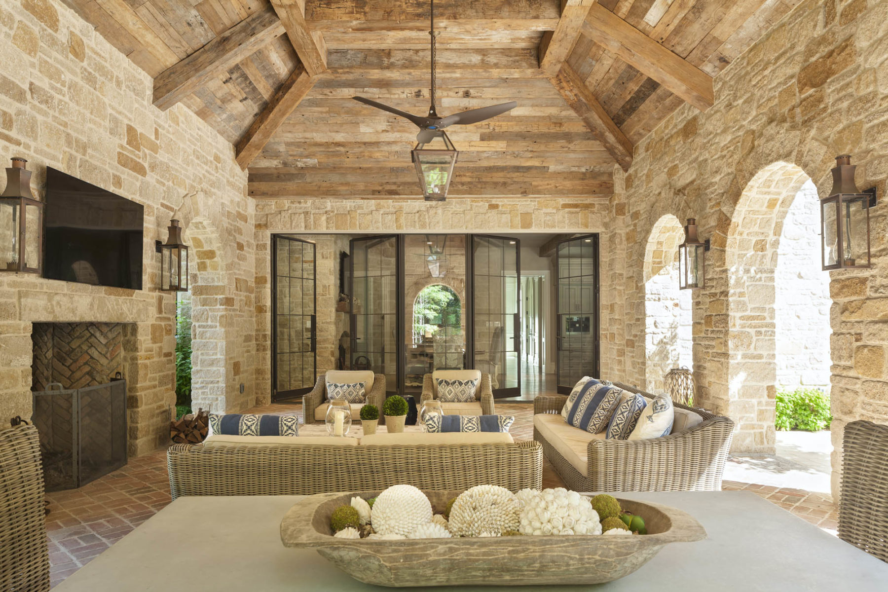 Loggia by Harrison Design has oak timbered vaulted ceiling, stone arches and herringbone brick floor with outdoor fireplace