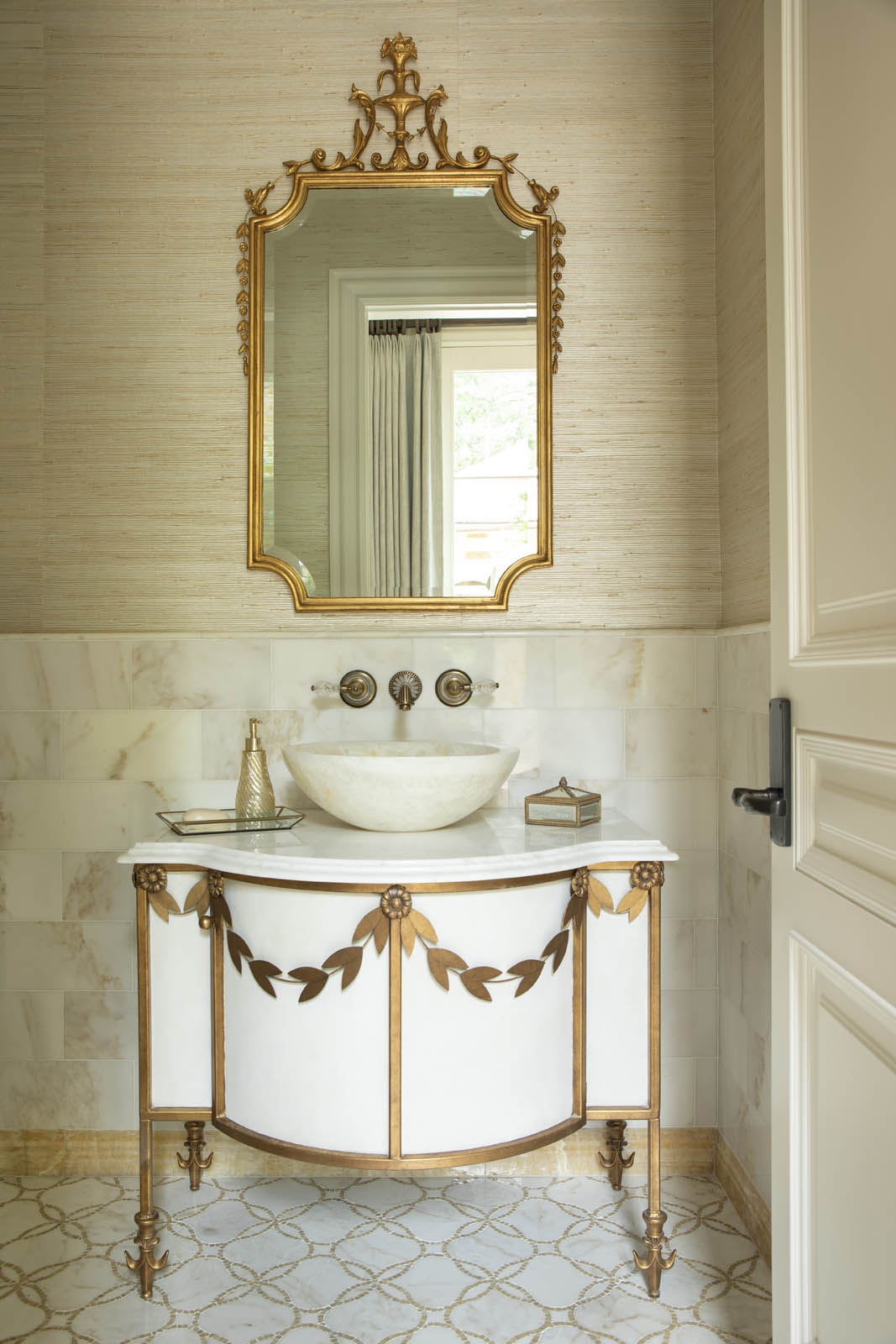 Powder room has French Empire motif decorated laurel leaves cabinet gilt brass mirror and inlaid floor by Harrison Design