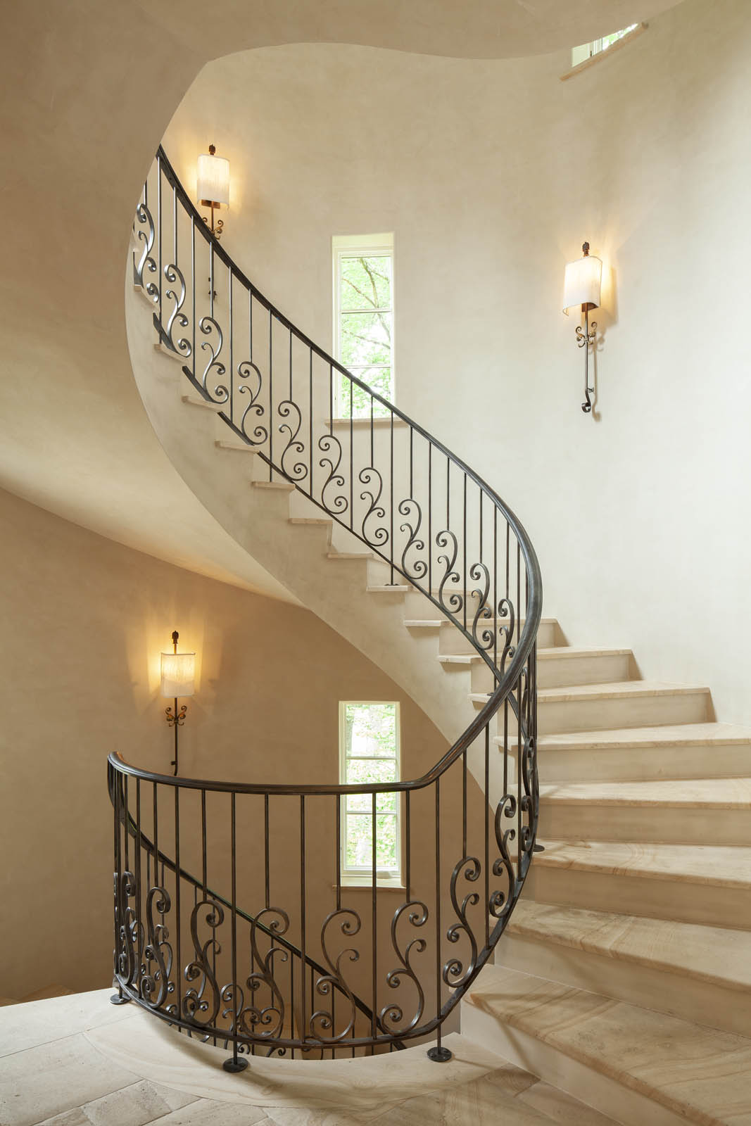 Windows in the turret illuminate staircase with wrought iron railing and decorative scrollwork by Harrison Design
