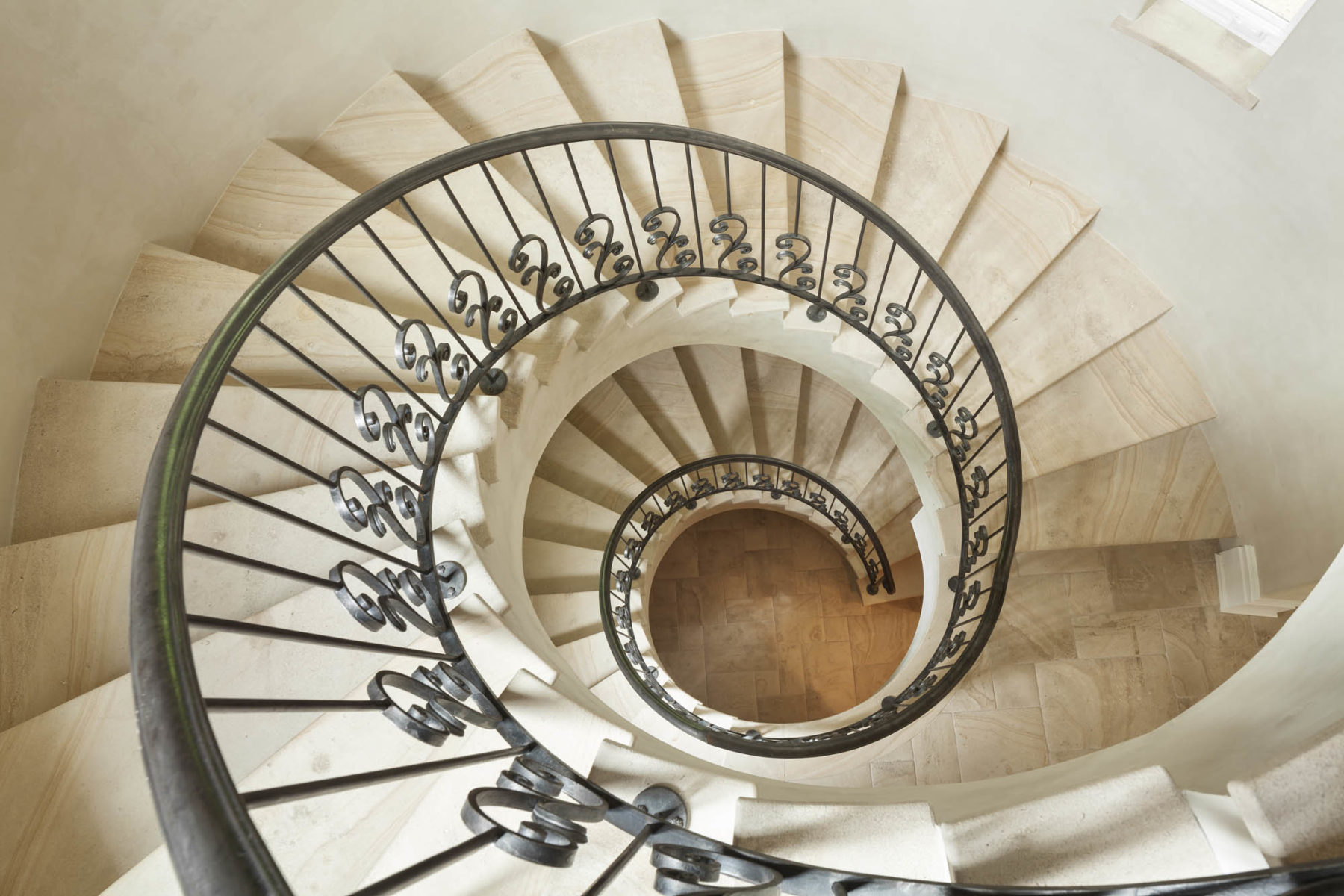 Dramatic spiral staircase made of wrought iron and limestone in this Harrison Design rustic estate home
