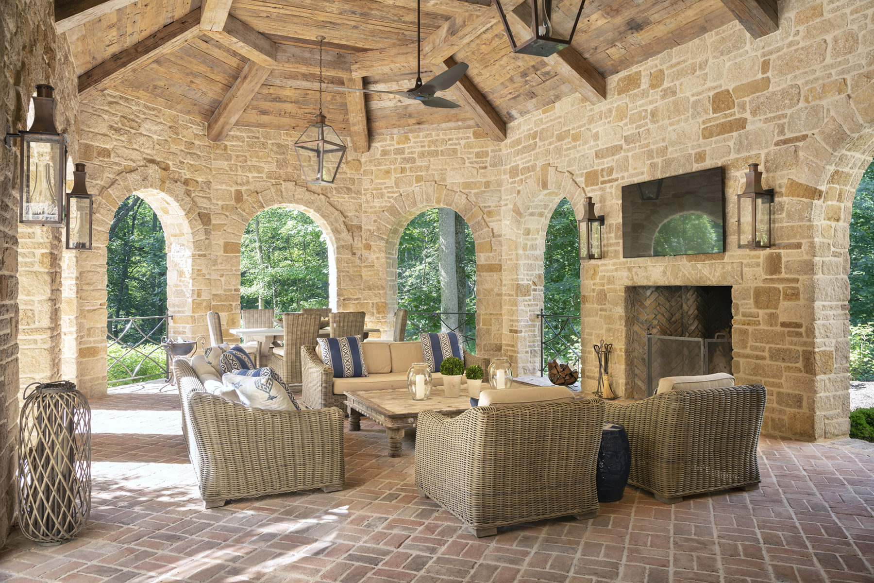 Harrison Design Indoor outdoor relaxed living with covered terrace stone archways and wood clad high ceiling with wood beams