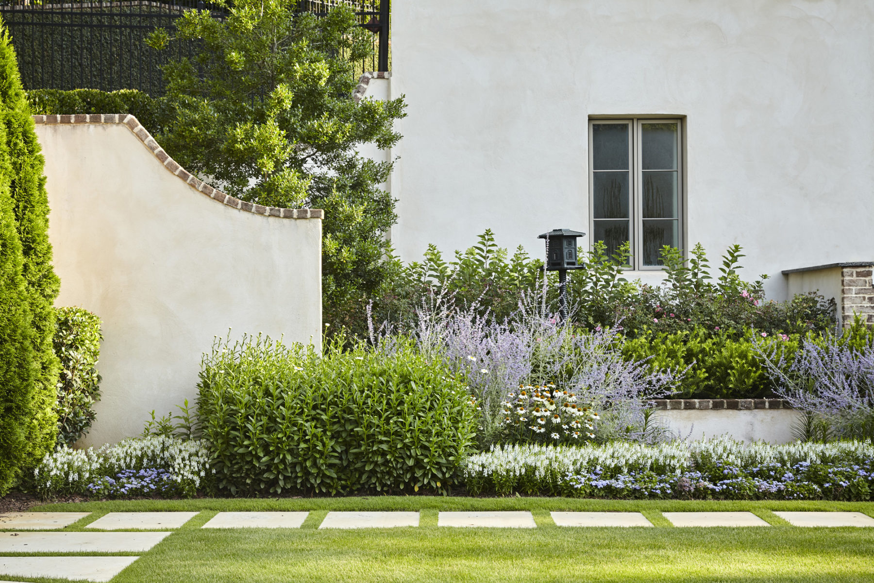 Relaxed English style perennial border in garden with Russian sage, Becky daisy and Holly in estate by Harrison Design