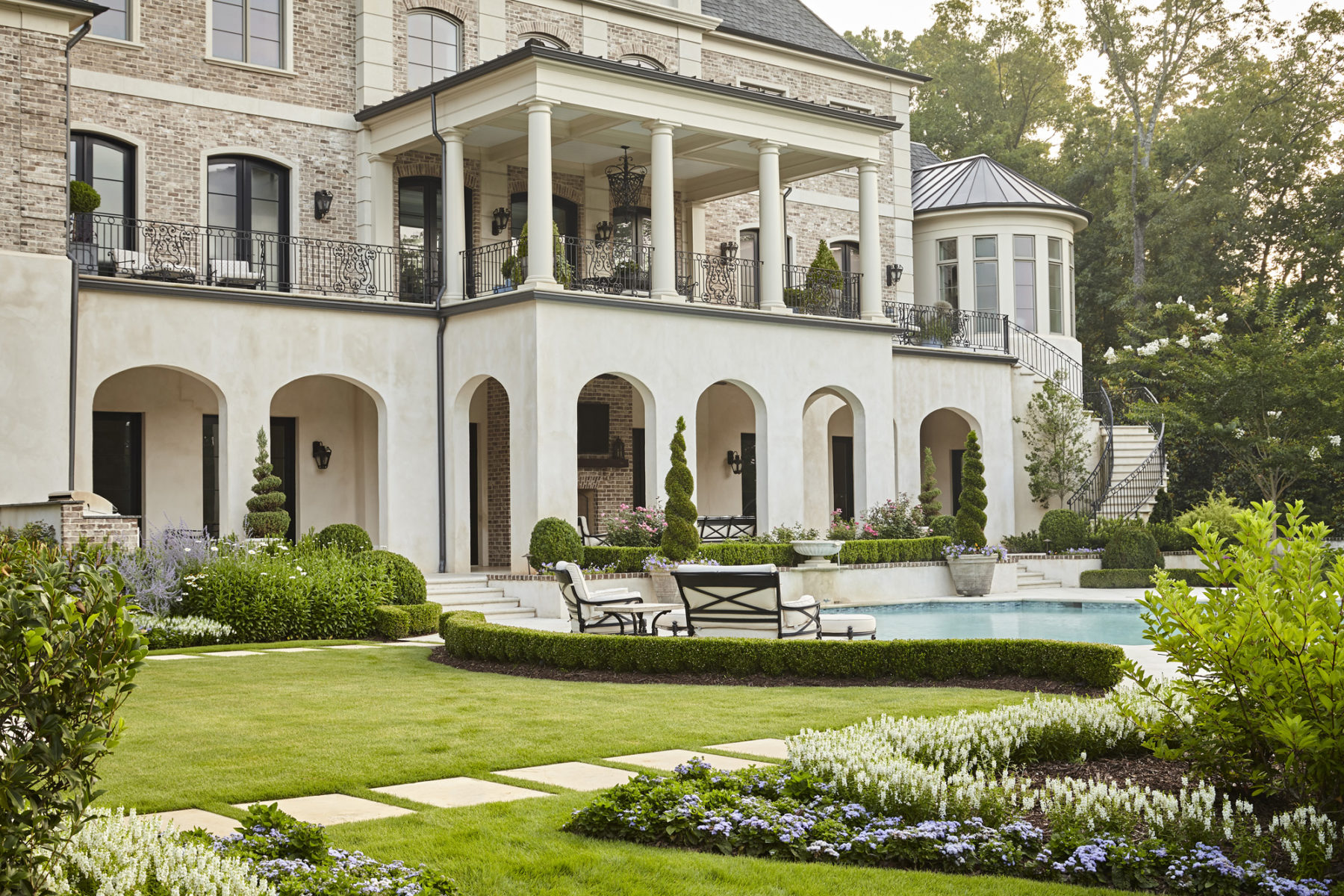 Curved clipped boxwood echoes quatrefoil pool with arched loggia and second floor terrace in neoclassical Harrison Design home