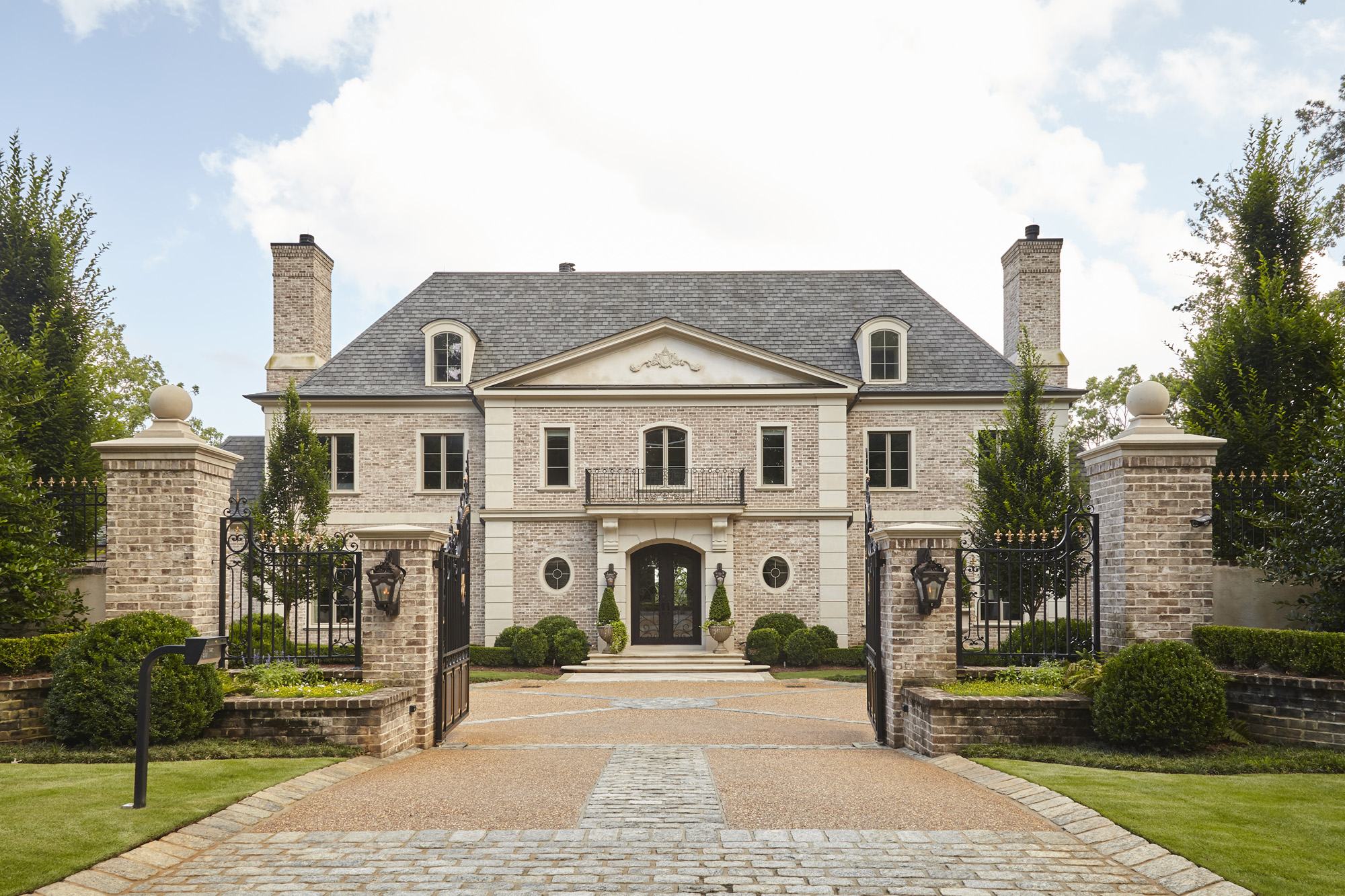 Stately formality in European inspired house from Harrison Design with gated entry brick facade and formal landscape